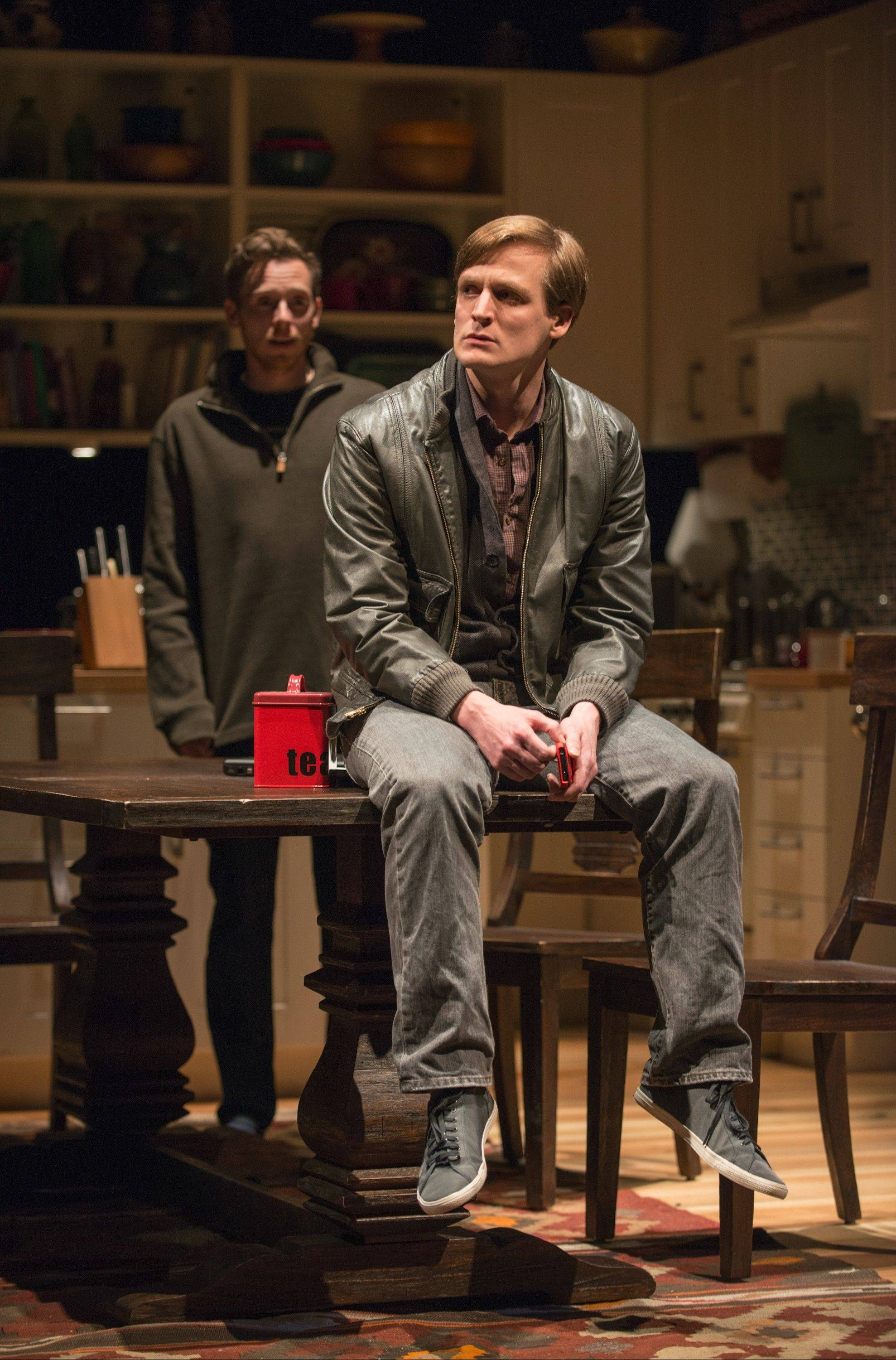 "John McGinty, foreground, plays Billy, a deaf young man whose recent immersion in the Deaf community causes a schism in his family and distresses older brother Daniel (Steve Haggard), background, in Nina Raine's ""Tribes,"" running through Feb. 9 at Steppenwolf Theatre."