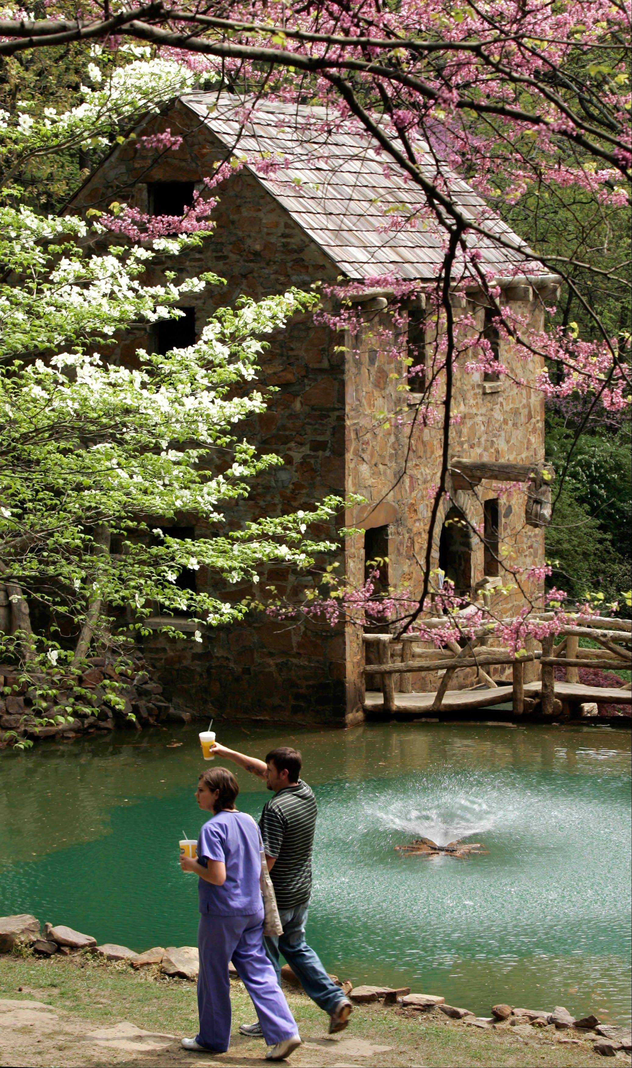 "A couple strolls past The Old Mill, which was featured in the film ""Gone With the Wind."" Picnics and photo shoots are often held at the scenic site, one of a number of free things to see and do in Little Rock, Ark."