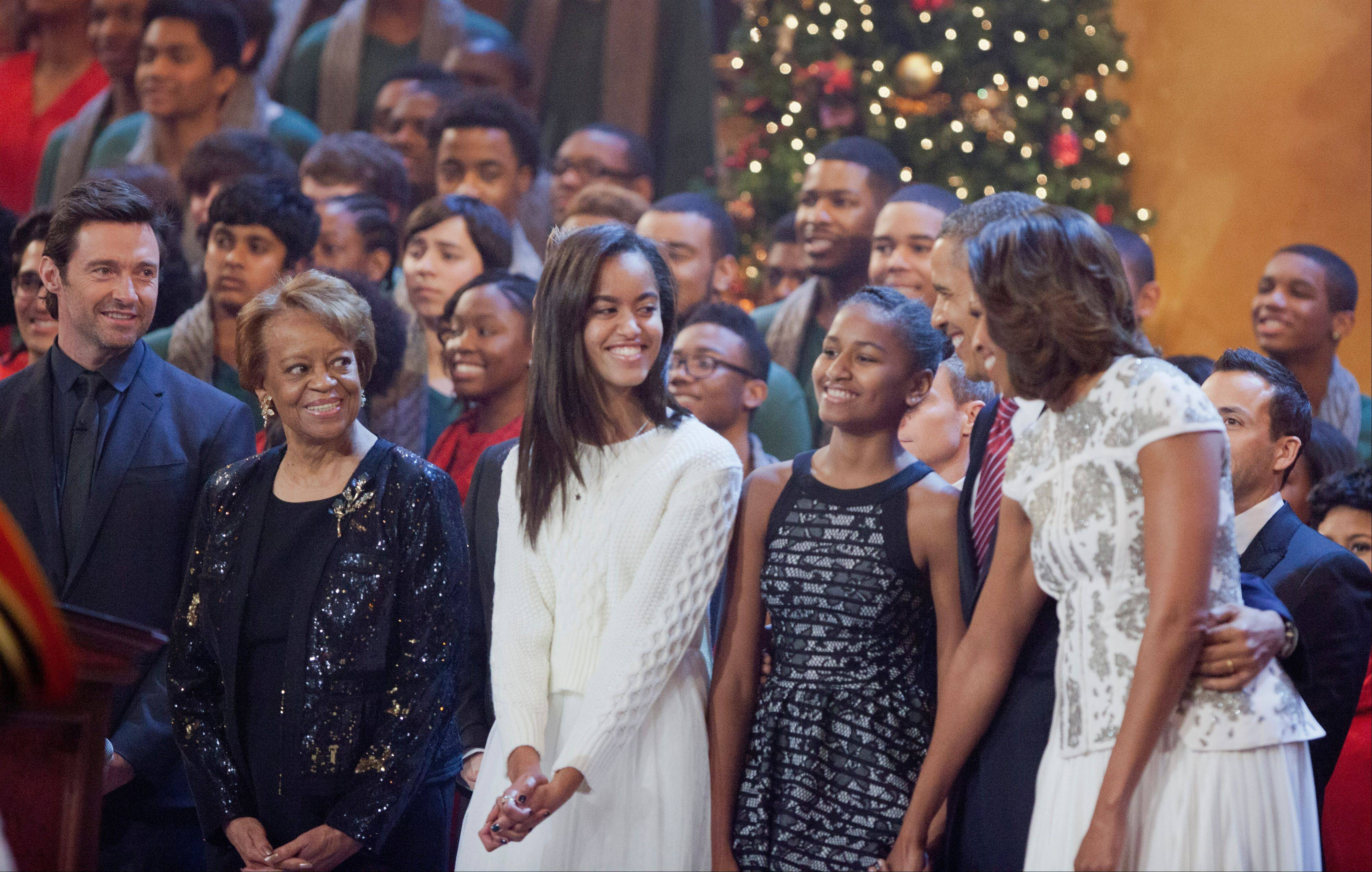 Host Hugh Jackman, left, and the first family, from second left, Marian Robinson, Malia Obama, Sasha Obama, President Barack Obama and first lady Michelle Obama, join performers on the stage singing a Christmas carol during the annual 2013 Christmas in Washington presentation at the National Building Museum in Washington. It airs on TNT tonight.