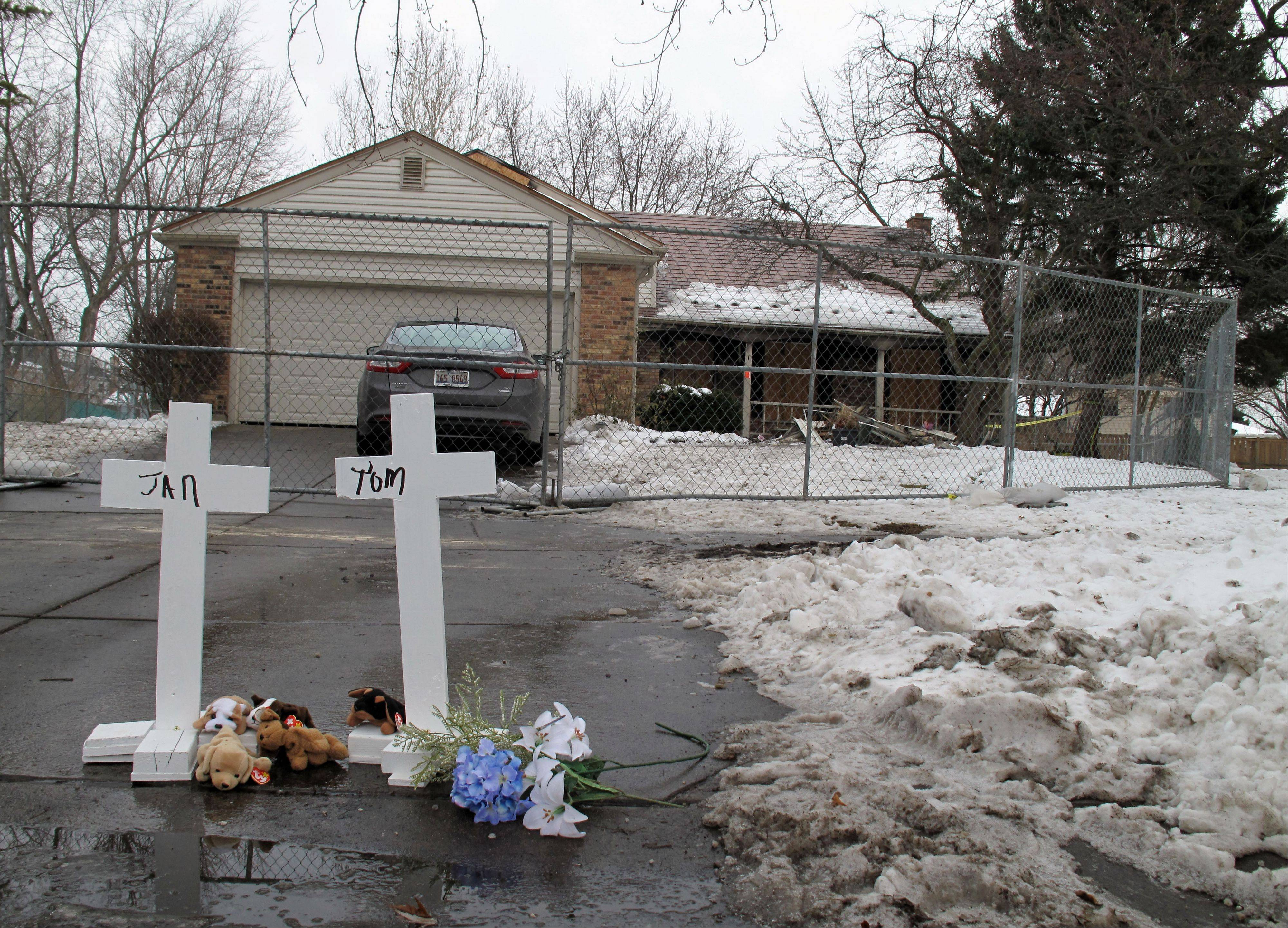 Crosses have been placed outside the Naperville home of Tom and Jan Lambert, where a fire Wednesday morning killed the couple and injured Tom's sister, father and a 21-year-old caregiver. The cause of the fire is still under investigation.