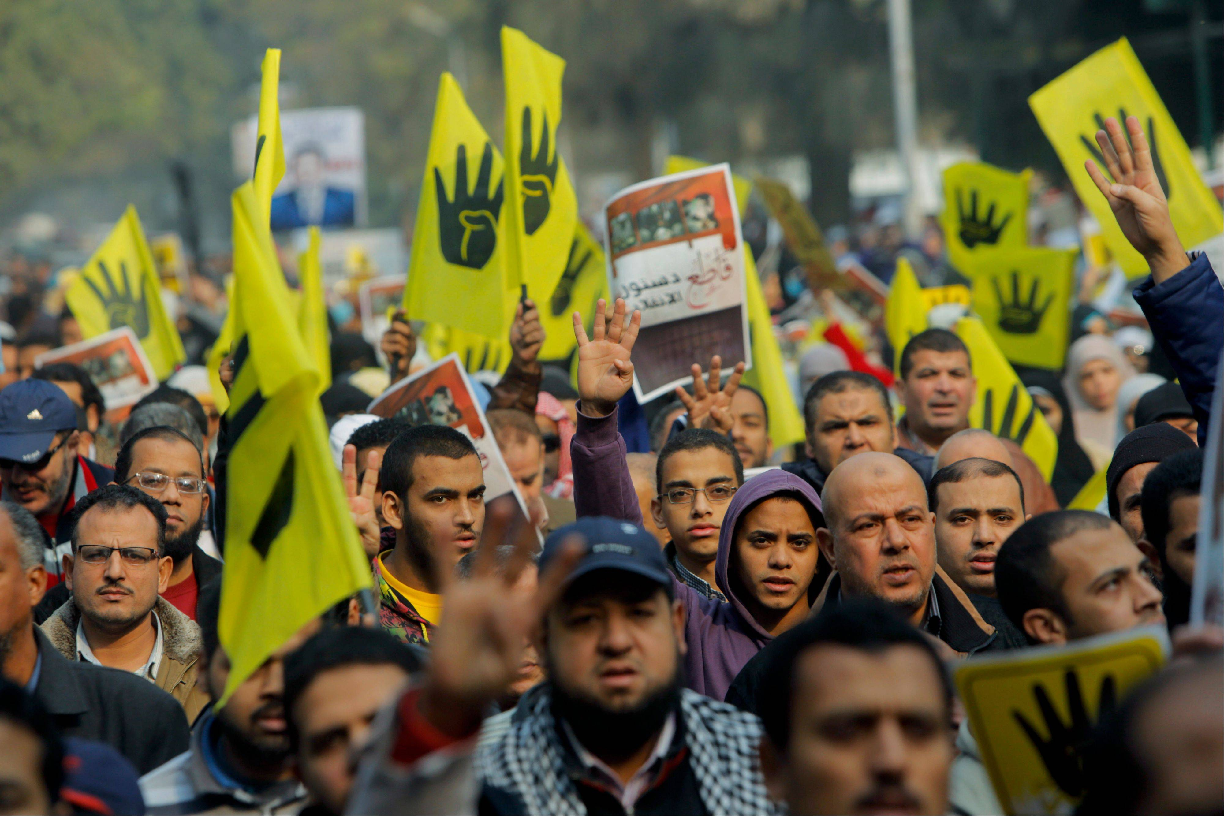 Supporters of Egypt's ousted President Mohammed Morsi raise flags Friday with a logo showing a hand with four raised fingers which has become a symbol of the Rabaah al-Adawiya mosque, where Morsi supporters had held a sit-in for weeks that was violently dispersed in August.