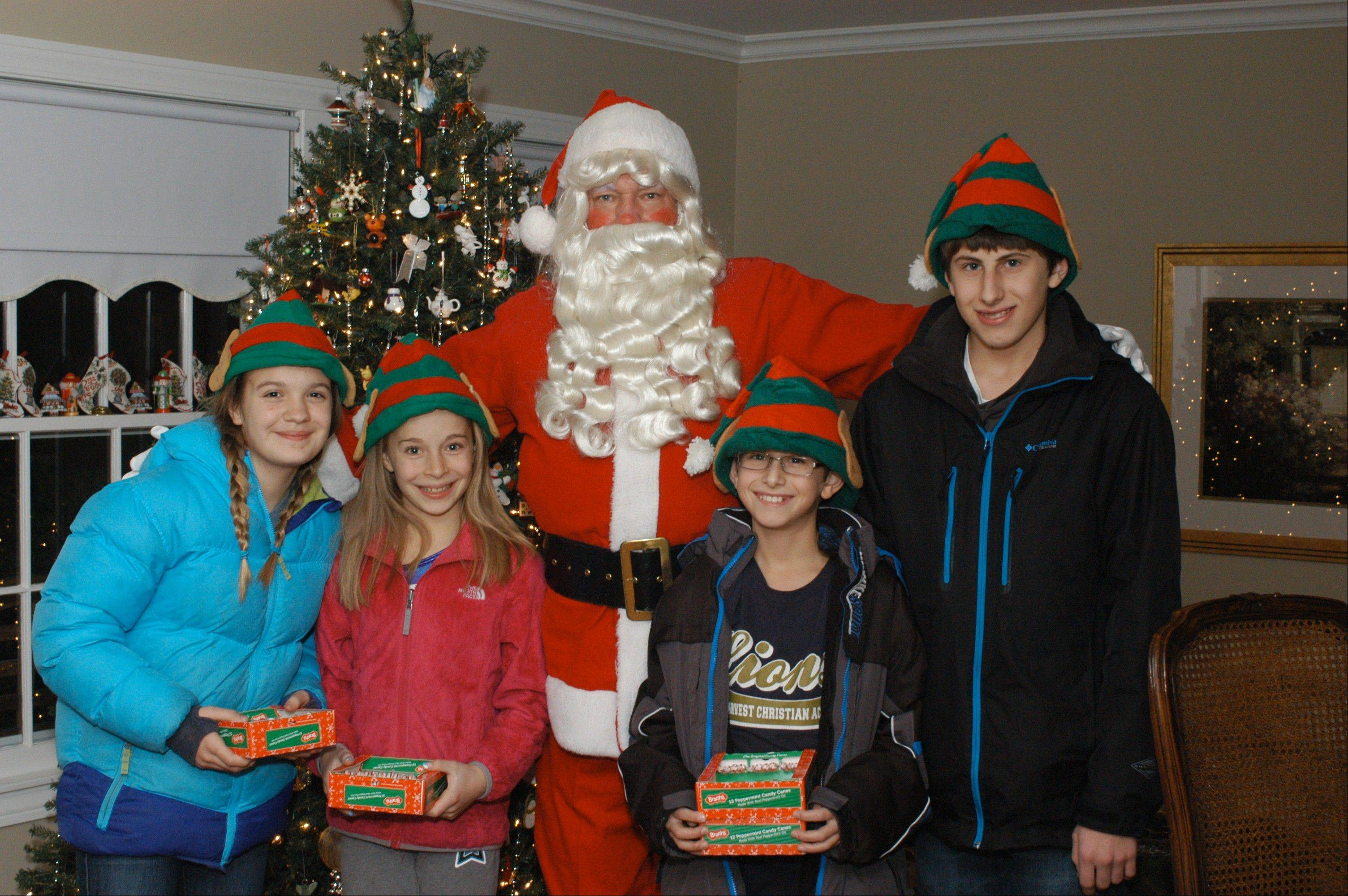 Santa, Paul Zillman of Palatine, finds his way to the right houses in the Willow Wood subdivision with the help of his elves, from left, Emmi Antonik, Samantha Mogensen, Blake Nudo and Brent Nudo.