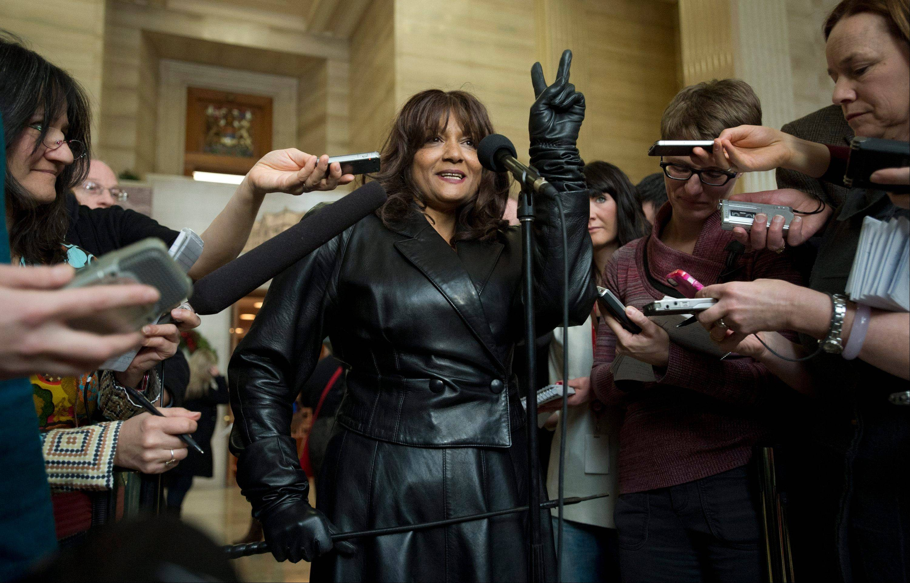 Terri-Jean Bedford gives a victory sigh as she talks to reporters at the Supreme Court of Canada in Ottawa Friday morning, Dec. 20, 2013 after learning Canada's highest court struck down the country's prostitution laws in their entirety in a unanimous 9-0 ruling. The retired dominatrix is one of the three principles in the Supreme Court case.