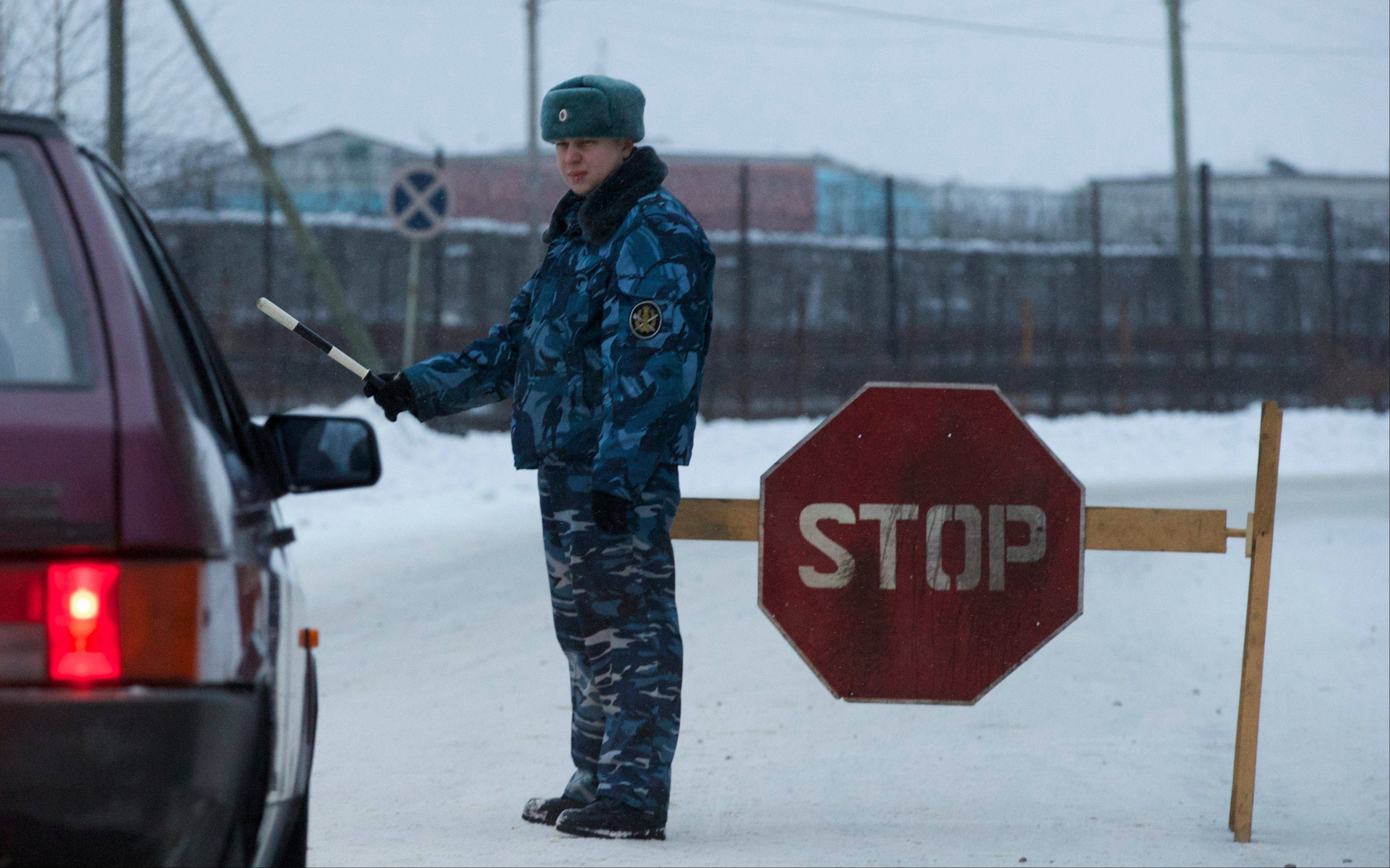 A prison service officer stops a car on the road at the prison where Mikhail Khodorkovsky was kept in Segezha, near Petrozavodsk, Russia, Friday, Dec. 20, 2013. Russia's once richest man Mikhail Khodorkovsky, the arch rival of President Vladimir Putin, has been released from prison after a decade behind bars, his spokeswoman told the Associated Press on Friday.