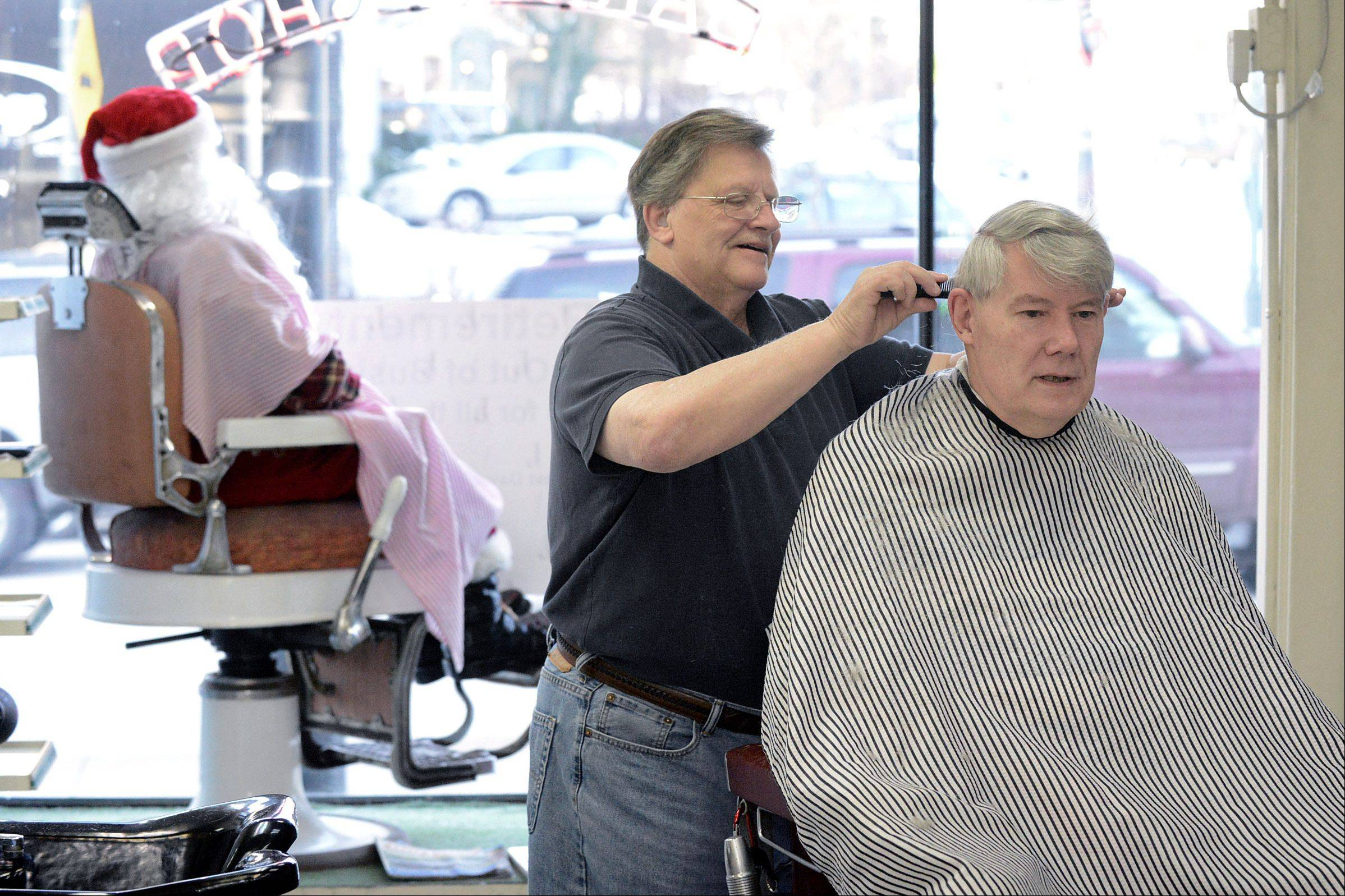 Barber Ron Saltzgiver gives William Hardey of North Aurora a trim in his shop Wednesday. After 45 year in St. Charles, Saltzgiver is retiring. Hardey and Saltzgiver have known each other since 1953 when they both attended Mooseheart in Batavia. After returning from Vietnam in 1968, Saltzgiver bought Berry's Barbershop, which first opened in 1910. The shop will close Saturday.