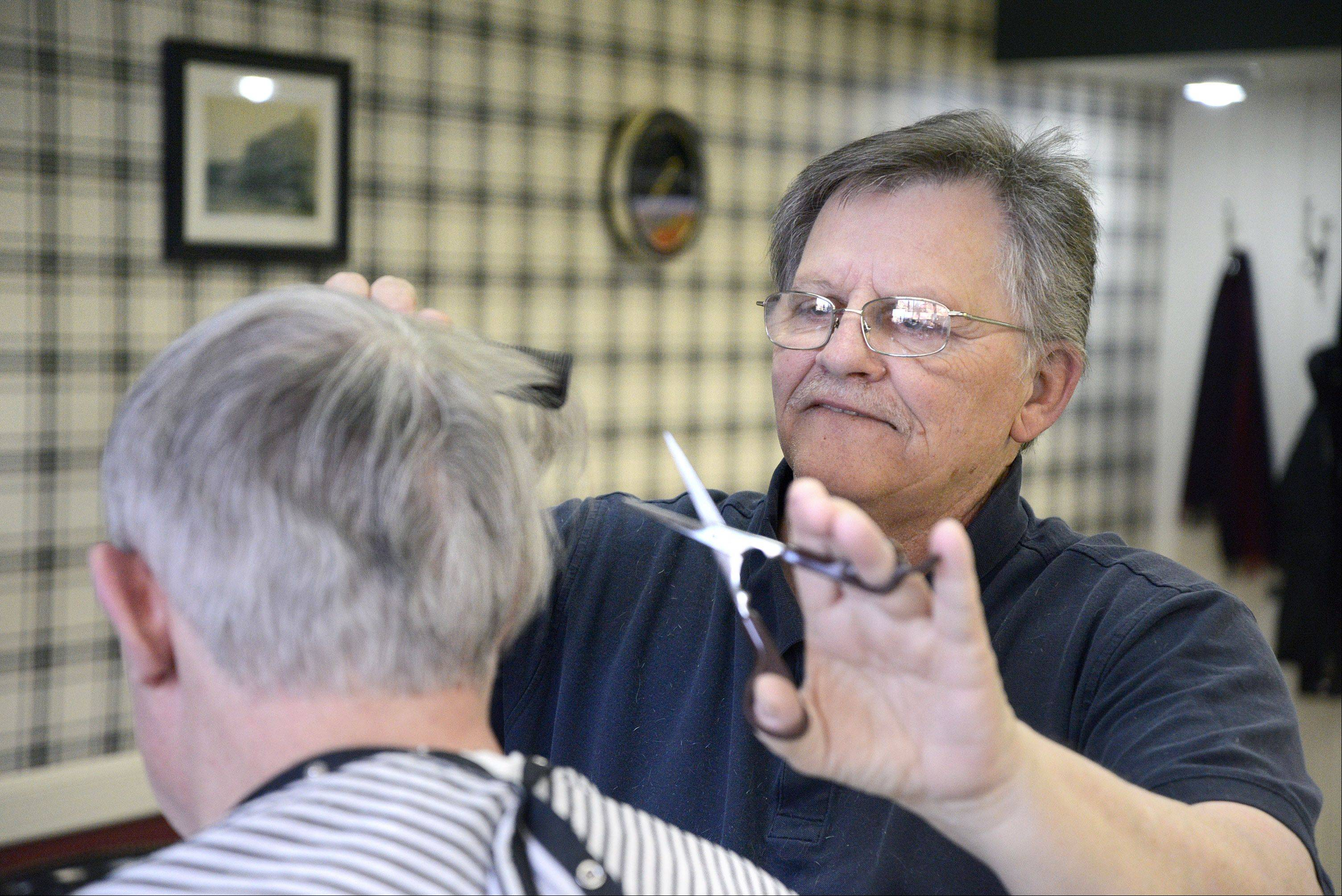 Barber Ron Saltzgiver gives William Hardey of North Aurora a trim in his shop this week. Saltzgiver is closing Berry's Barbershop Saturday. Busy to the end, Hardey was Saltzgiver's 18th of 26 clients Wednesday.