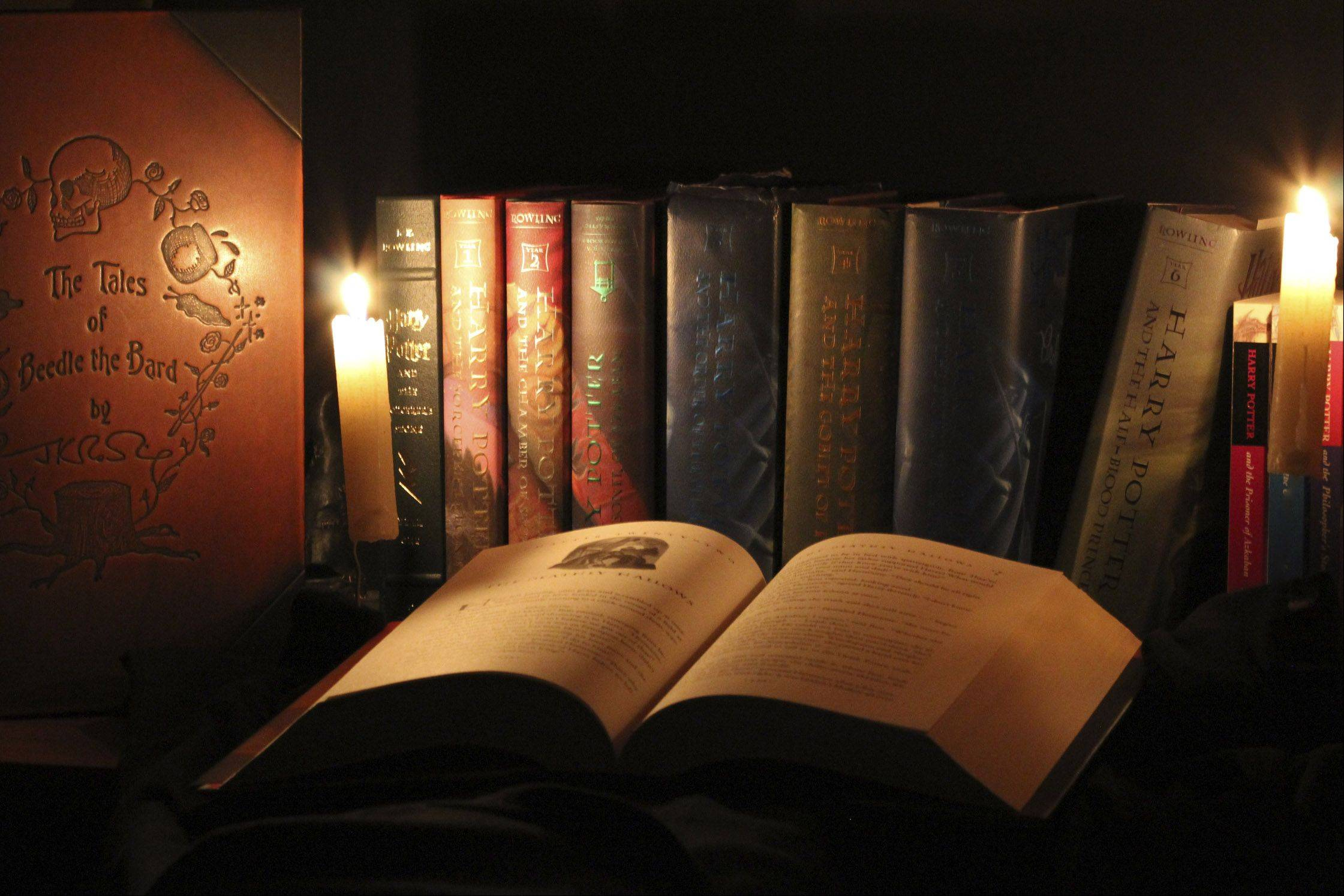 A group Harry Potter books are illuminated with candles to give them a magical look.