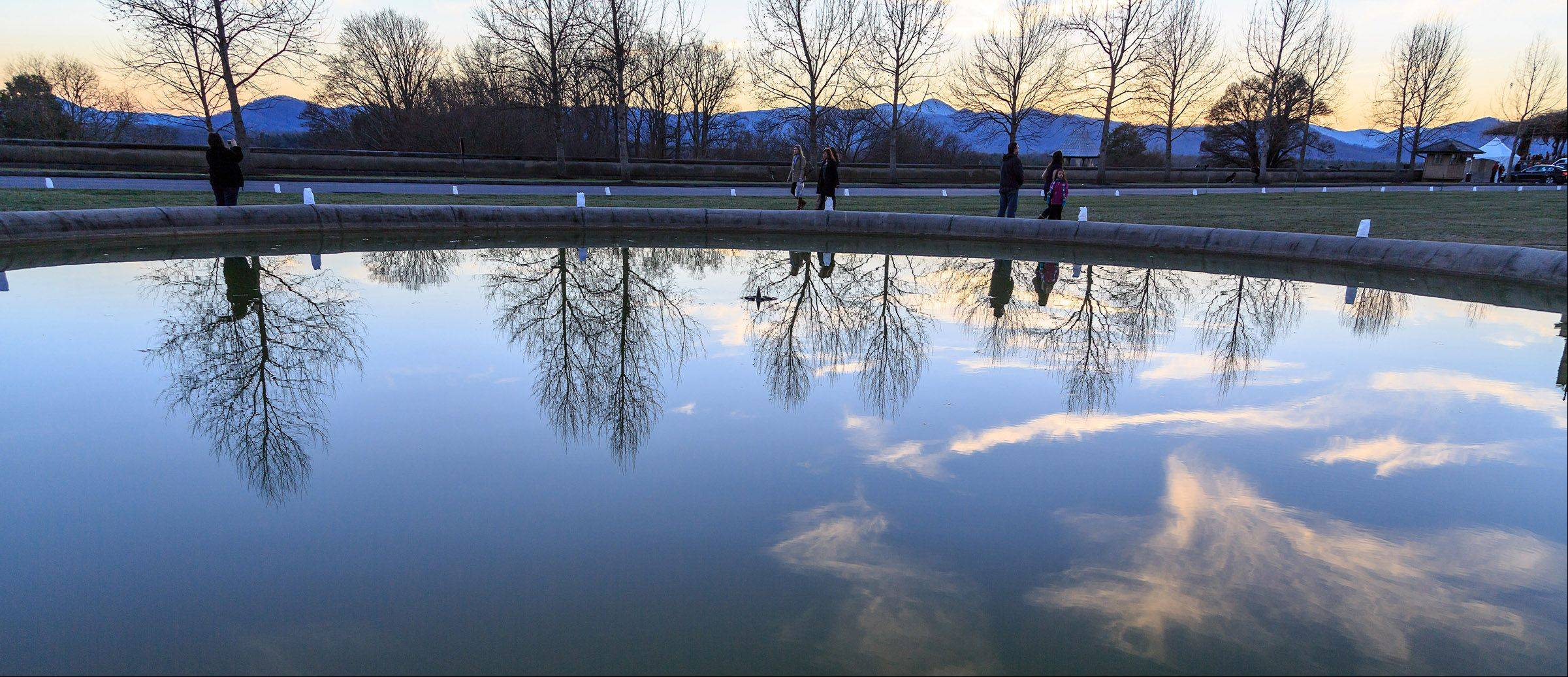 Trees are reflected in the water under a dusk sky in the large pond in front of the Biltmore House at Biltmore Estates in Asheville, NC on November 29. The Blue Ridge Mountains are in the background.