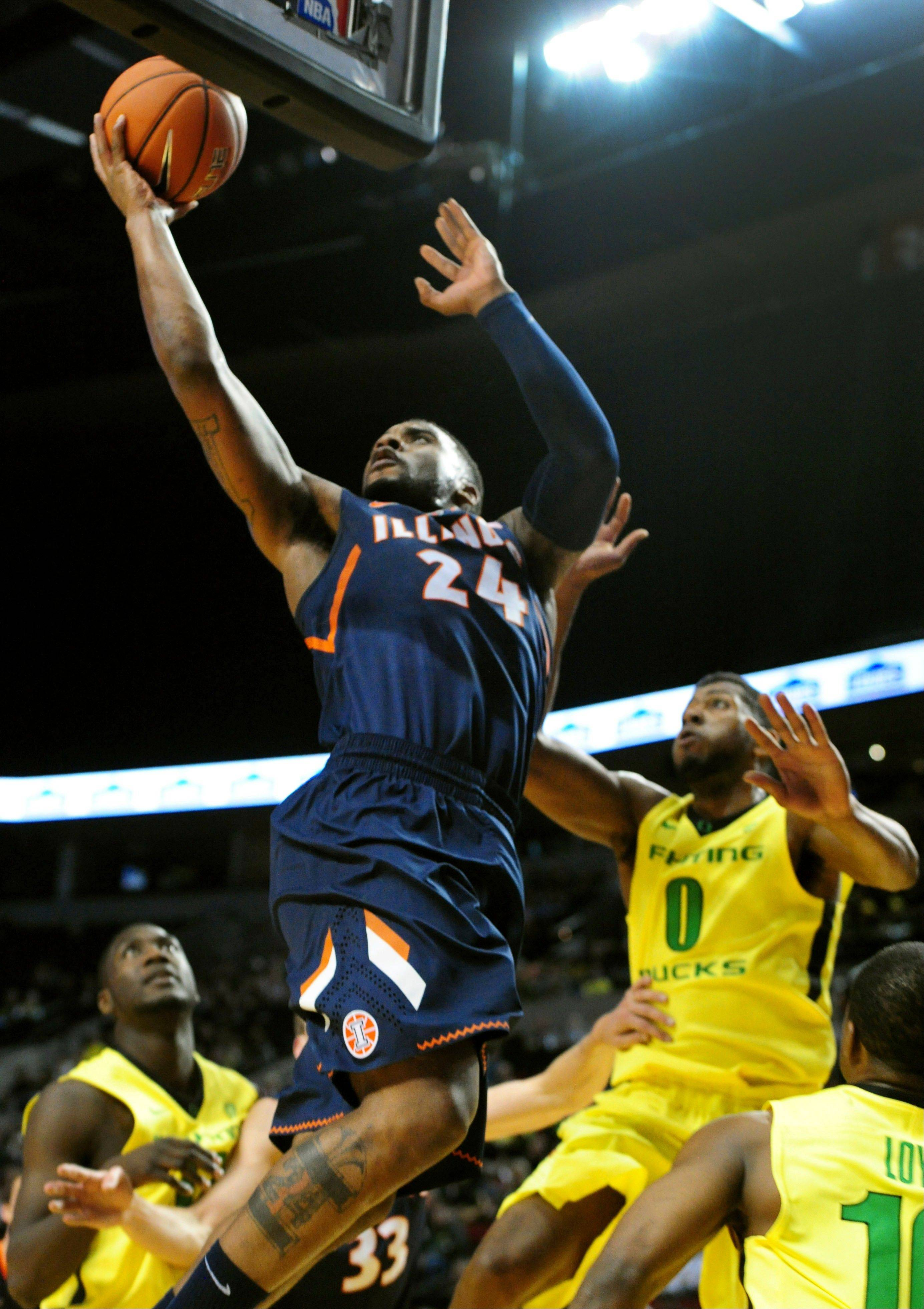 Illinois guard Rayvonte Rice (24) drives to the basket on Oregon guard Mike Moser during the first half of an NCAA college basketball game in Portland, Or., Saturday, Dec. 14, 2013.