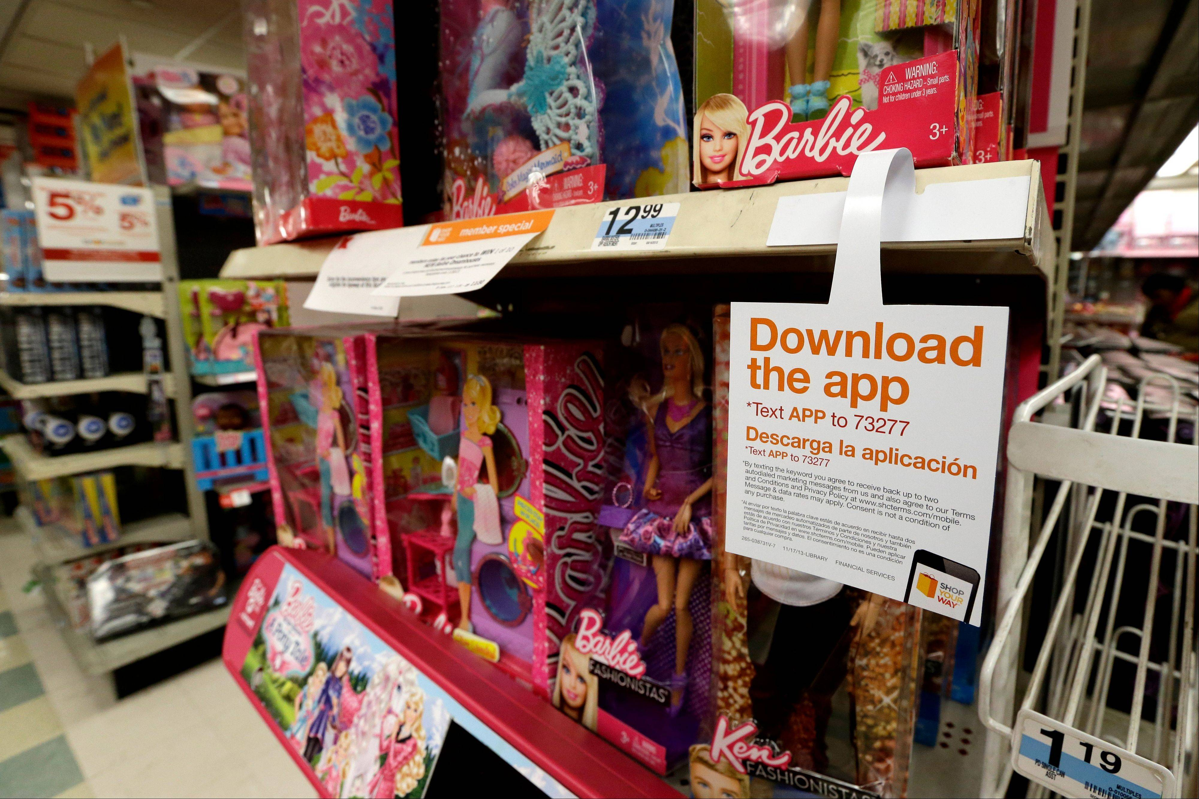 A sign for a shopping application is placed at the toys section in Kmart, in New York. Mobile shopping accounts for about 10 percent of online sales this season, but it made up half of all online traffic during Black Friday weekend, according to IBM Benchmark.