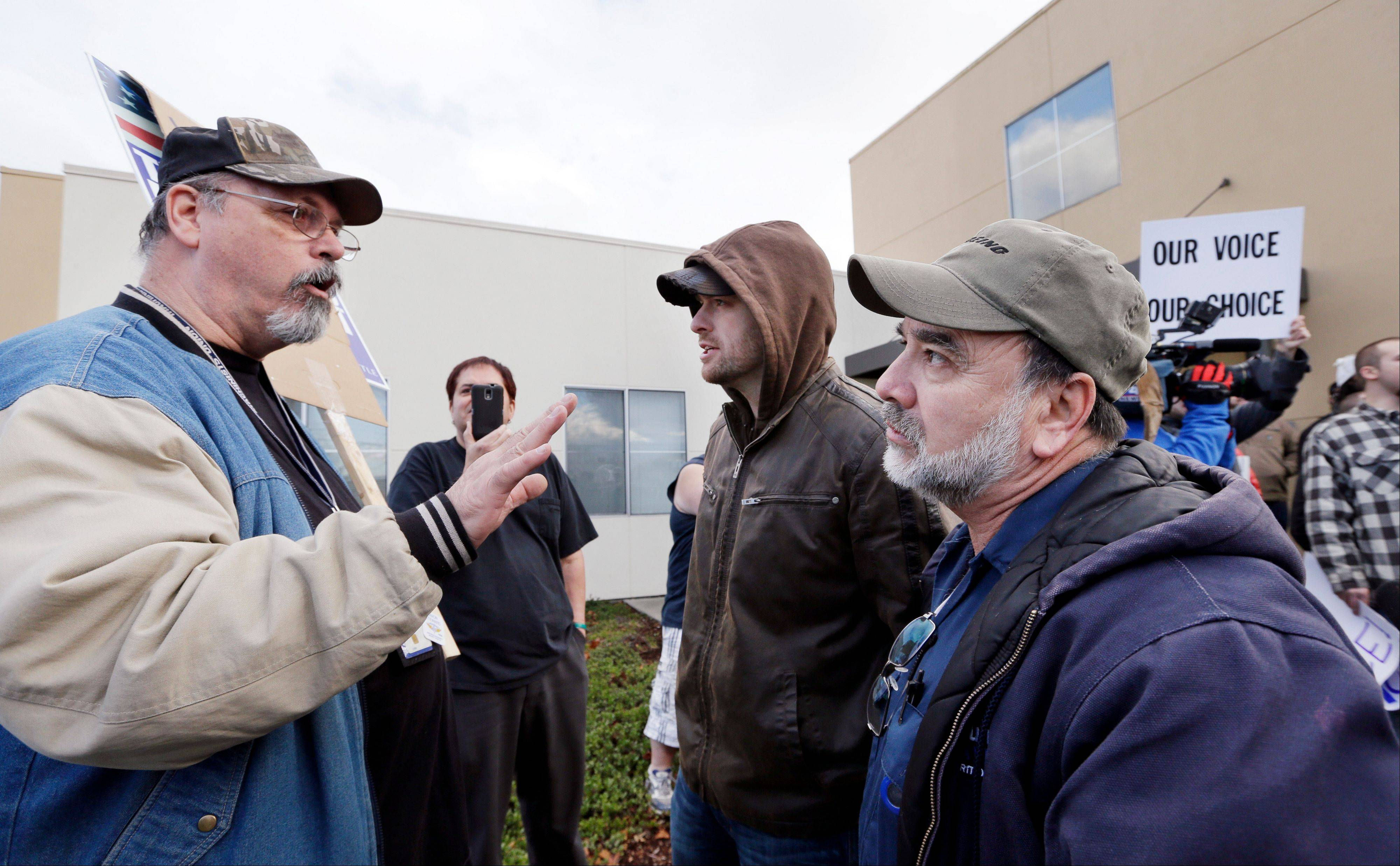 Machinists union shop steward Lester Mullen, left, explains the leadership position as he talks Wednesday with a small group of machinists union members who had rallied in favor of voting on Boeing�s last contract offer, in front of the machinists� union hall.