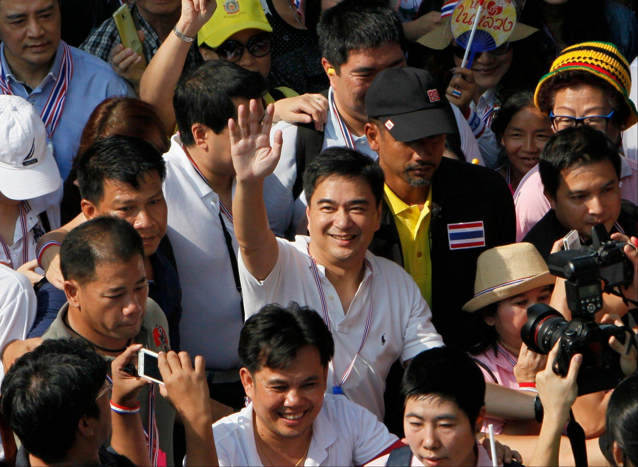 Associated Press Democrat leader and former Prime Minister Abhisit Vejjajiva, center, in this photo from Dec. 9, 2013, waves as he marches with anti-government protesters in Bangkok. The party�s leader Abhisit Vejjajiva announced the boycott after a meeting Saturday, Dec. 21, of party executives. He said the decision was made to try to ensure political reforms are implemented.
