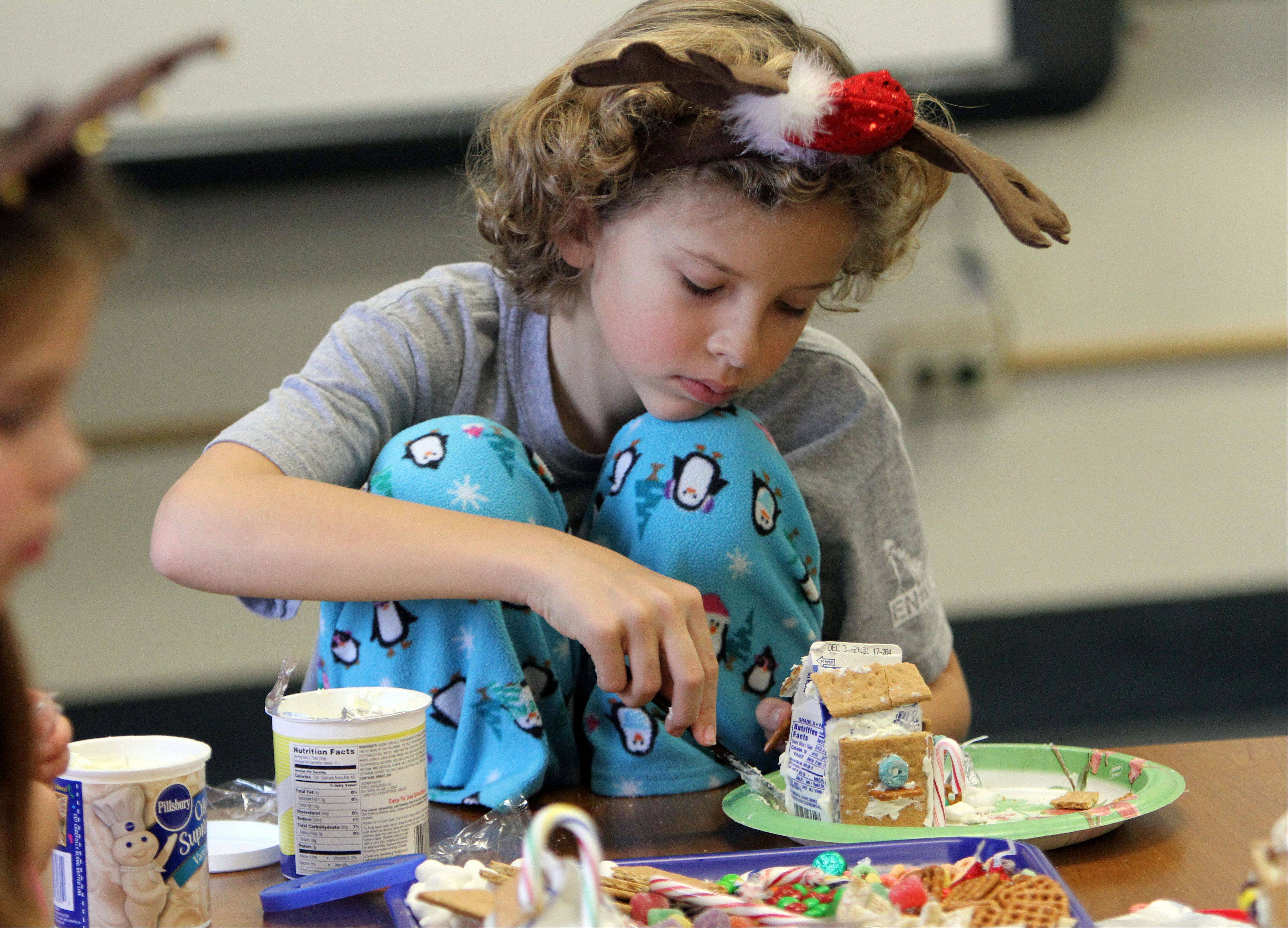 Rockland School fifth-grader Jamie Nicholson works on her gingerbread house as the fifth- and first-graders teamed up on the project in Libertyville.