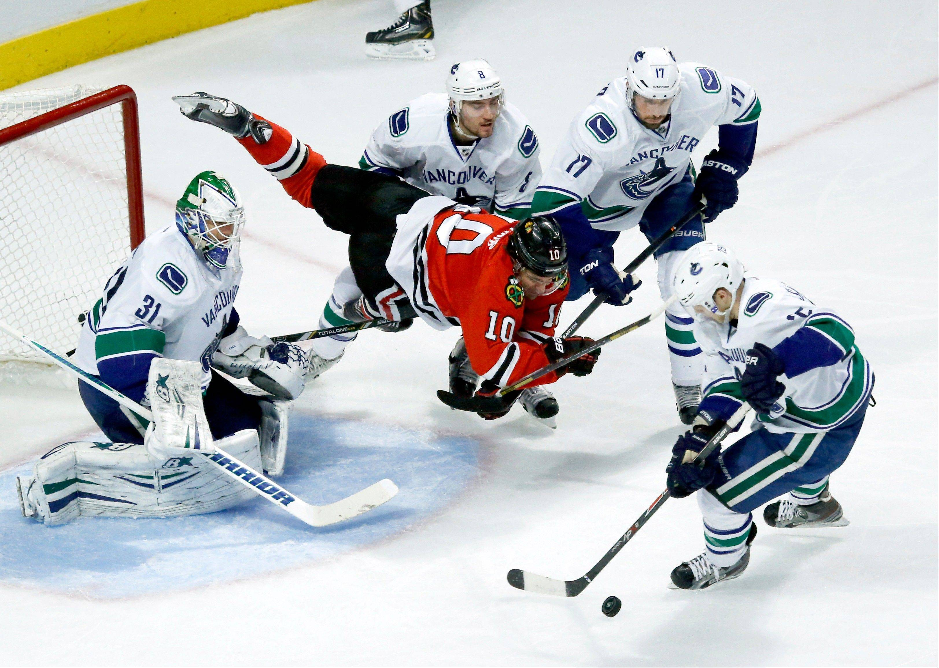 Canucks center Mike Santorelli, right, clears the puck after the Blackhawks� Patrick Sharp tried to split the defense of goalie Eddie Lack, Chris Tanev (8) and Ryan Kesler (17) in the third period Friday night.