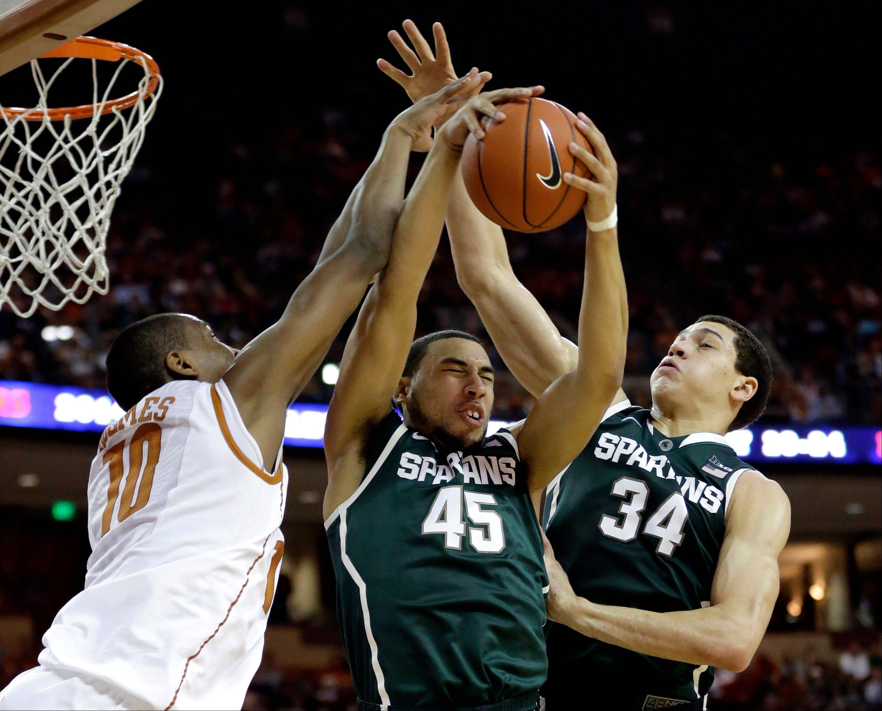 Michigan State�s Denzel Valentine (45) pulls in a rebound between teammate Gavin Schilling and Texas� Jonathan Holmes during the first half of Saturday�s game in Austin, Texas.