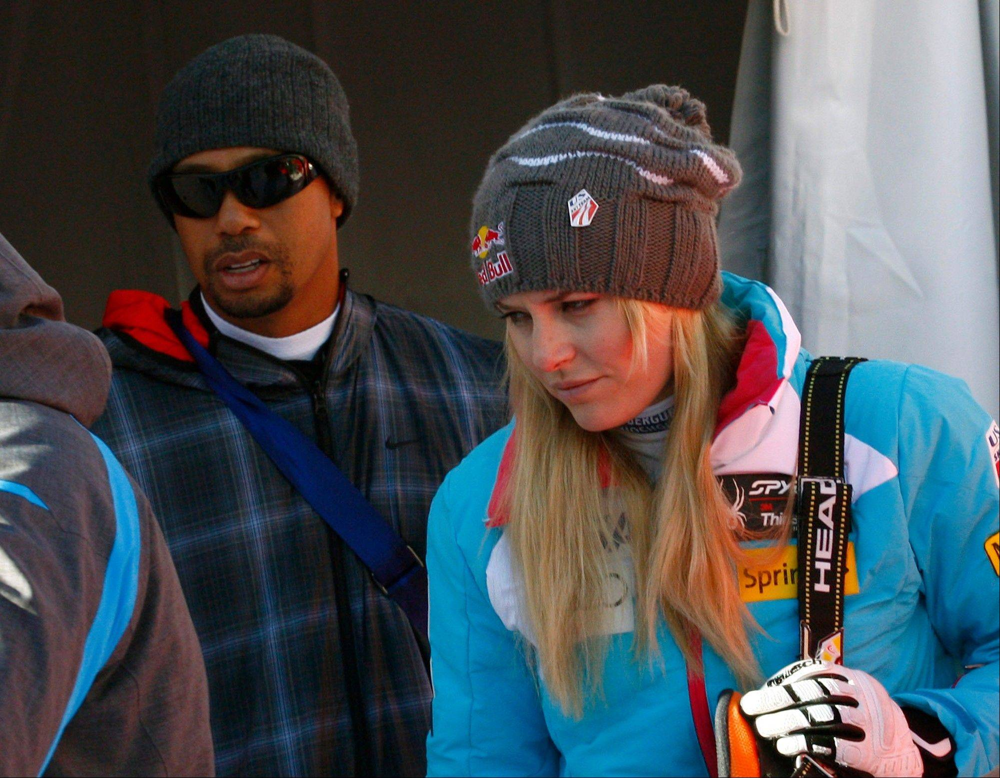 Lindsey Vonn is flanked by her boyfriend Tiger Woods as she leaves after an alpine ski, women's World Cup downhill, in Val D'Isere, France, Saturday, Dec. 21, 2013. Lindsey Vonn is confident that her latest knee trouble will not stop her from competing at the Sochi Games in February. With boyfriend Tiger Woods watching from the bottom of the slope, Vonn missed a gate in Saturday's World Cup downhill at Val d'Isere as her troublesome right knee buckled under her and gave way. The American was clearly distressed after skiing off course and looked close to tears. She didn't fall but grimaced as she pulled up, clutching her knee. (AP Photo/Giovanni Auletta)