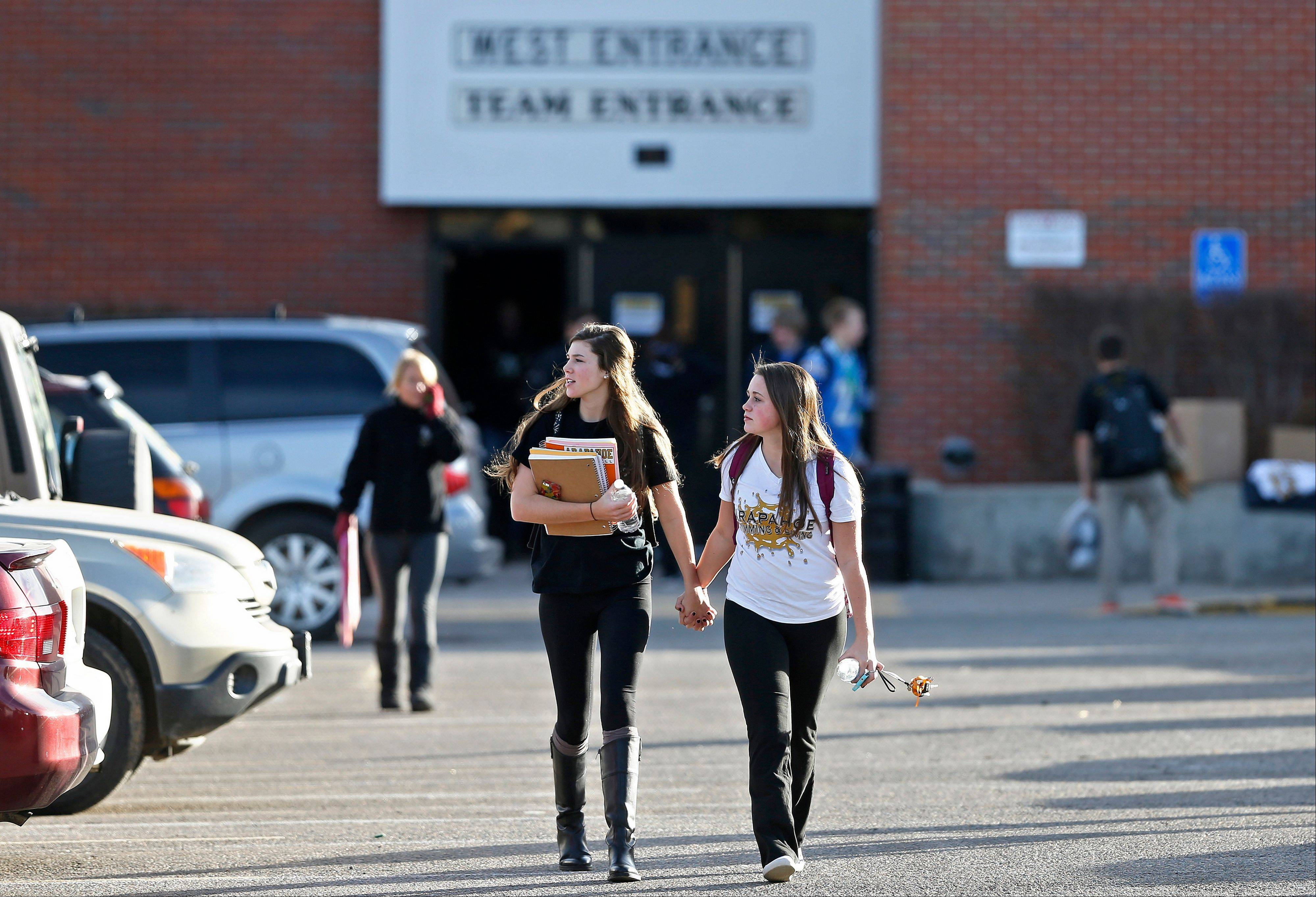 Arapahoe High School students leave their school Thursday on a day in which students were allowed back in to the building to retrieve their belongings, six days after a shooting attack at Arapahoe High School in Centennial, Colo.