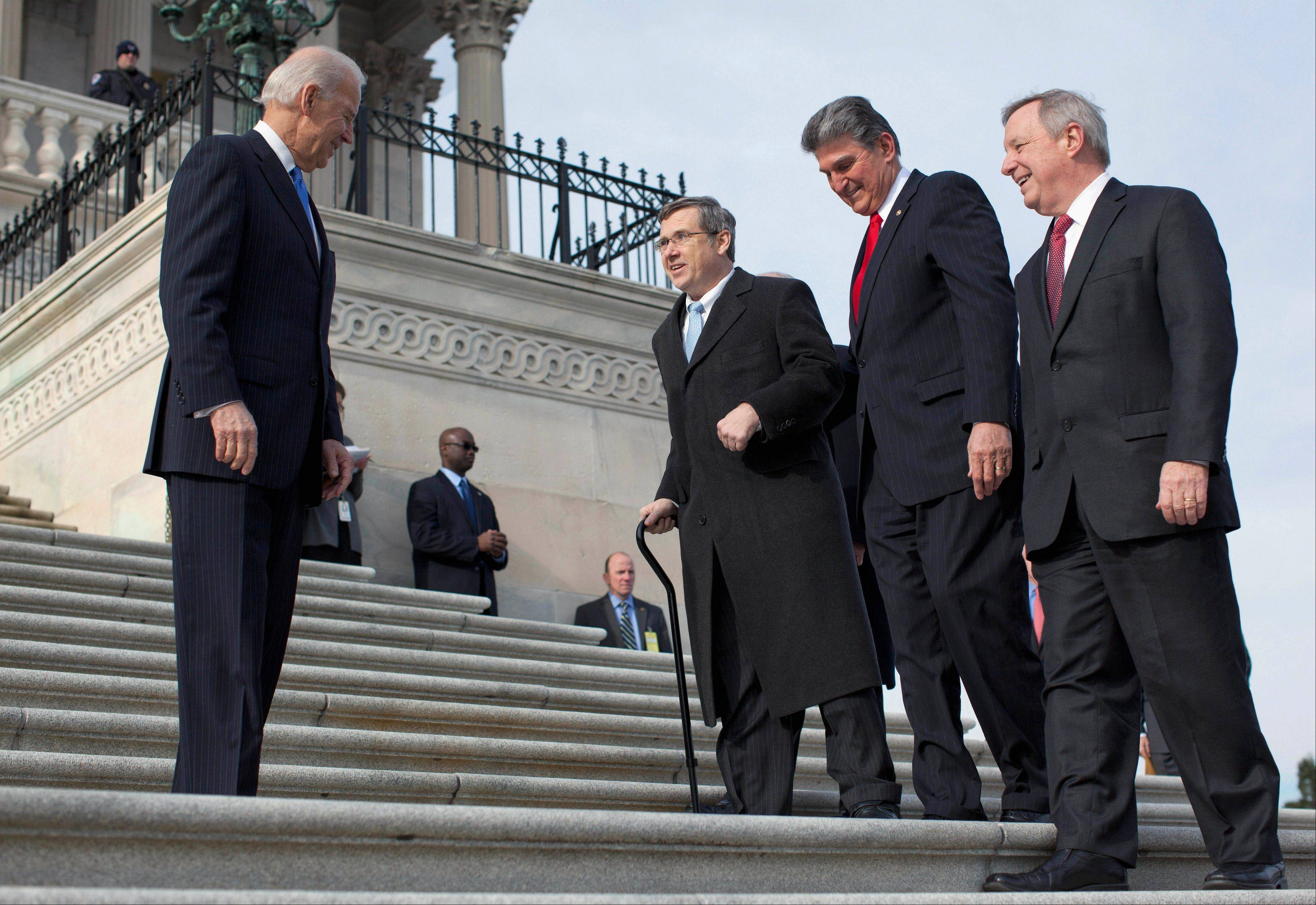 In this Jan. 3, 2013 file photo, Vice President Joe Biden watches at left as Sen. Mark Kirk, an Illinois Republican, second from left, accompanied by Sen. Joe Manchin, a West Virginia Democrat, second from right, and Senate Majority Whip Richard Durbin, an Illinois Democrat, right, walk the steps to the Senate door of the Capitol building in Washington a year after Kirk suffered a stroke. The two Illinois senators from opposing parties have worked together cordially since Kirk won President Barack Obama's former Senate seat in 2010. But the relationship has seemed to reach a new level after Kirk's stroke.