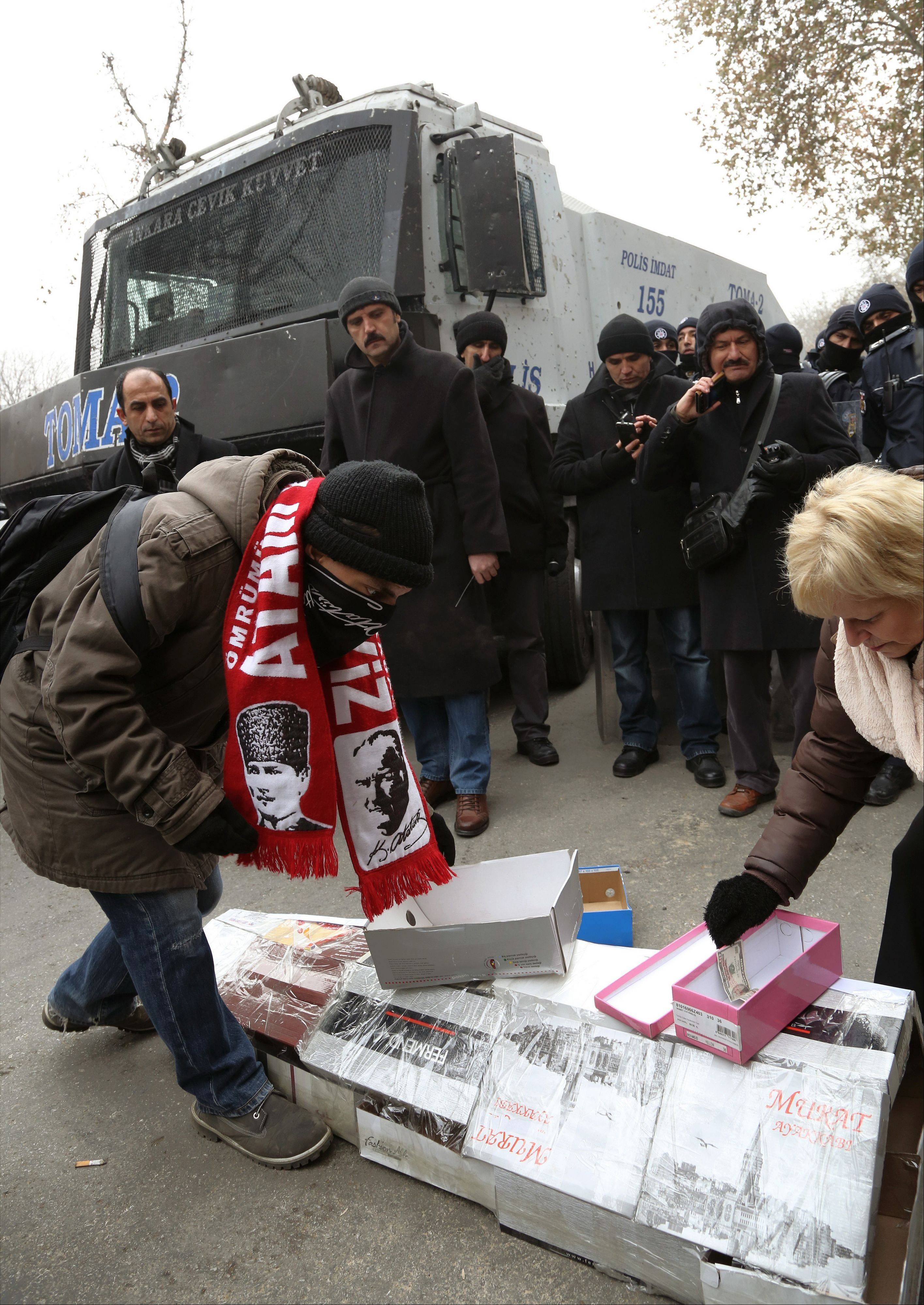 People leave more boxes on a casket made of empty shoe boxes in front of a security barricade during a protest in Ankara, Turkey, Saturday, Dec. 21. Police seized $4.5 million in cash stashed in shoe boxes at the residence of the chief executive officer of a state-owned bank as part of a corruption investigation.