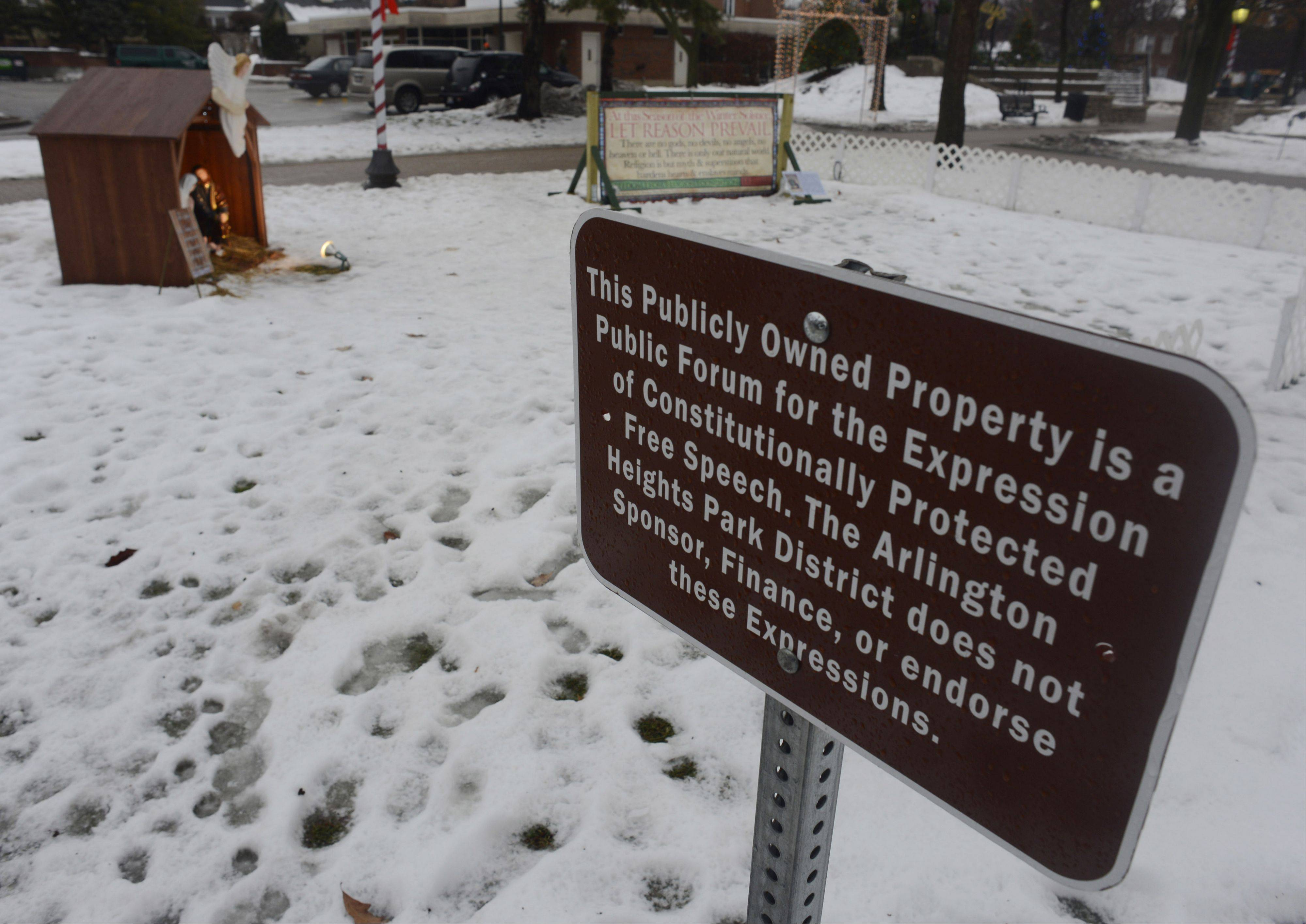 This sign, erected by the park district, serves as a disclaimer regarding a Nativity scene and a sign opposing religion in North School Park in Arlington Heights.