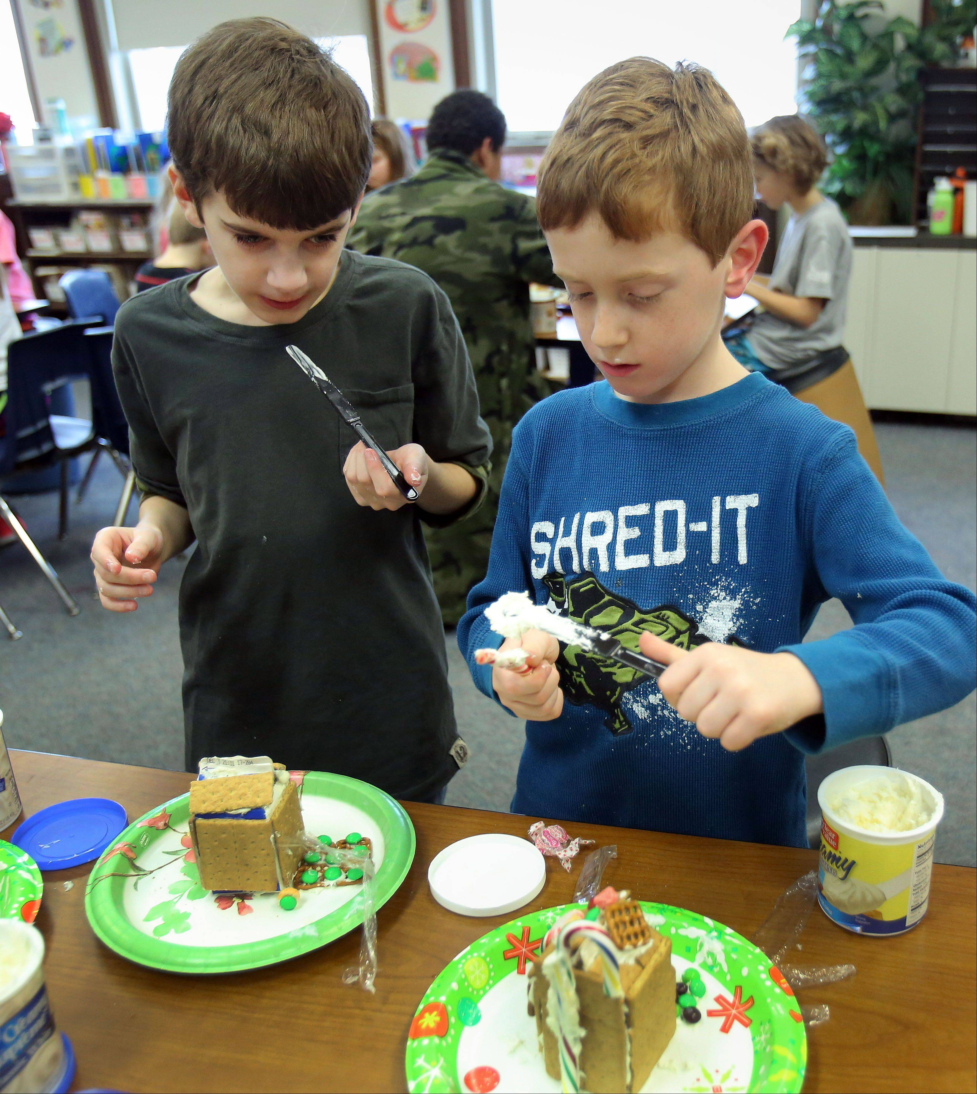 First-grader Jordan Coughlin, right, and his fifth grade book buddy, Ethan Early, work to create gingerbread houses at Rockland Elementary School in Libertyville.