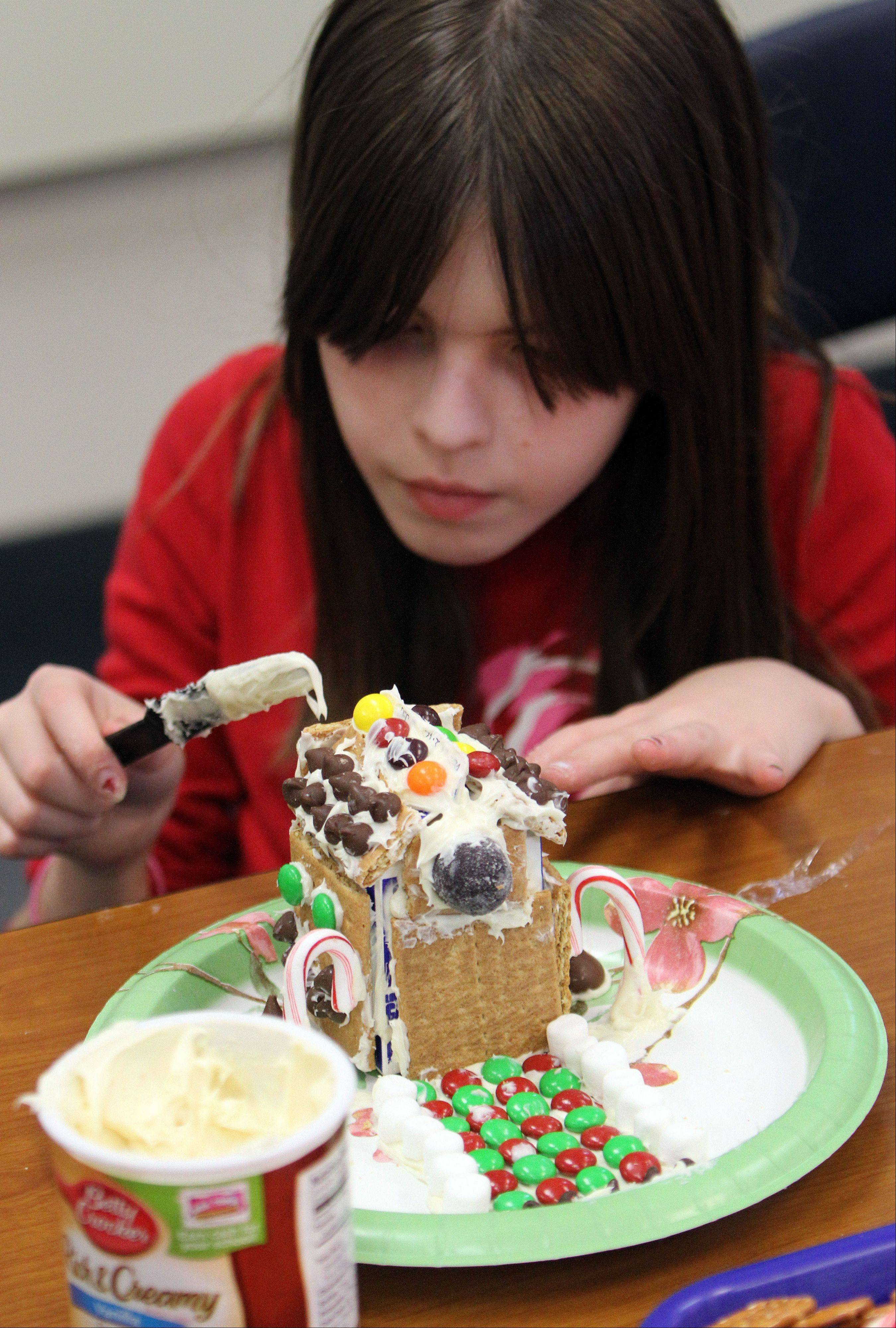 Rockland School fifth-grader Kylie Miller pays attention to detail as she creates her gingerbread house.