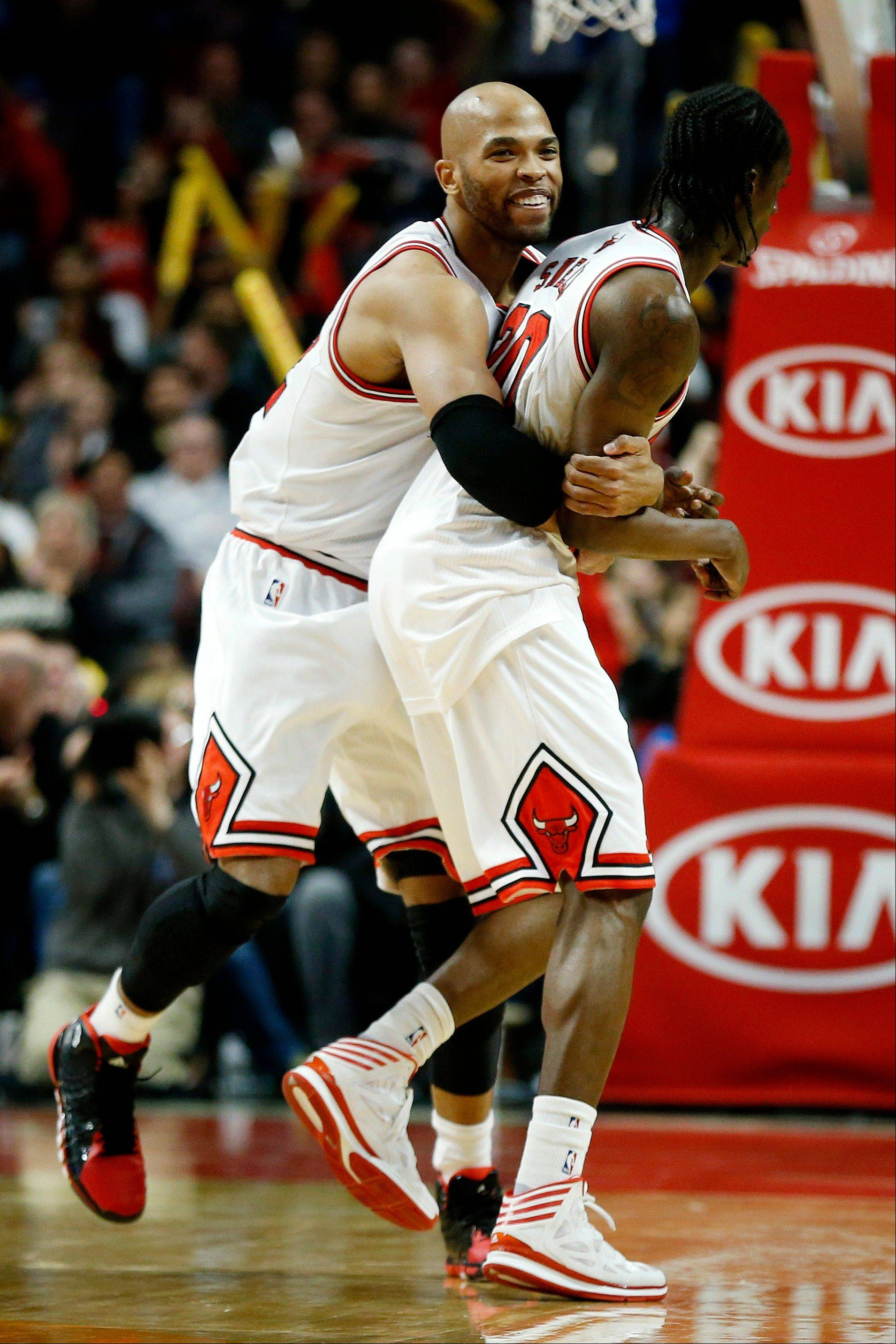 Bulls forward Taj Gibson, left, celebrates with Tony Snell, right, after Snell scored a 3-pointer during the second Saturday night at the United Center.