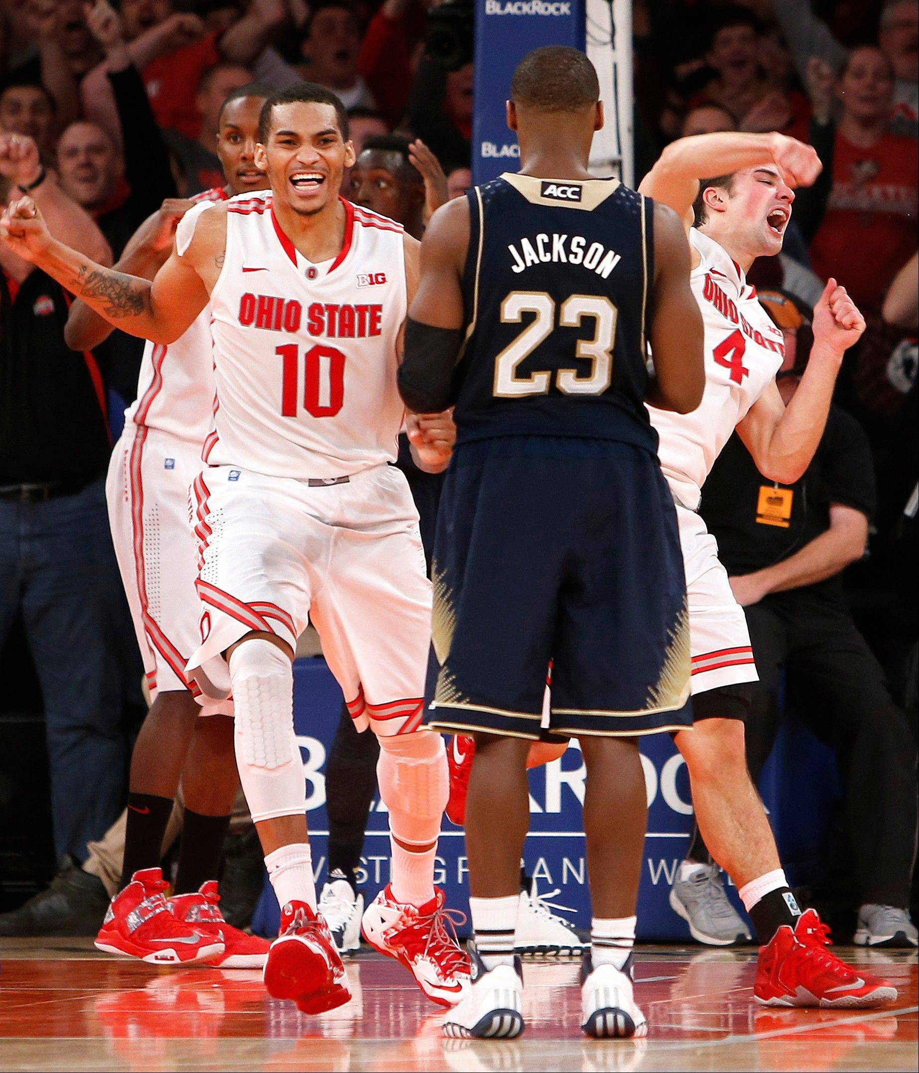 Ohio State's LaQuinton Ross and Aaron Craft celebrate after a turnover by Notre Dame in the final seconds of their game Saturday in New York. Ohio State won 64-61.