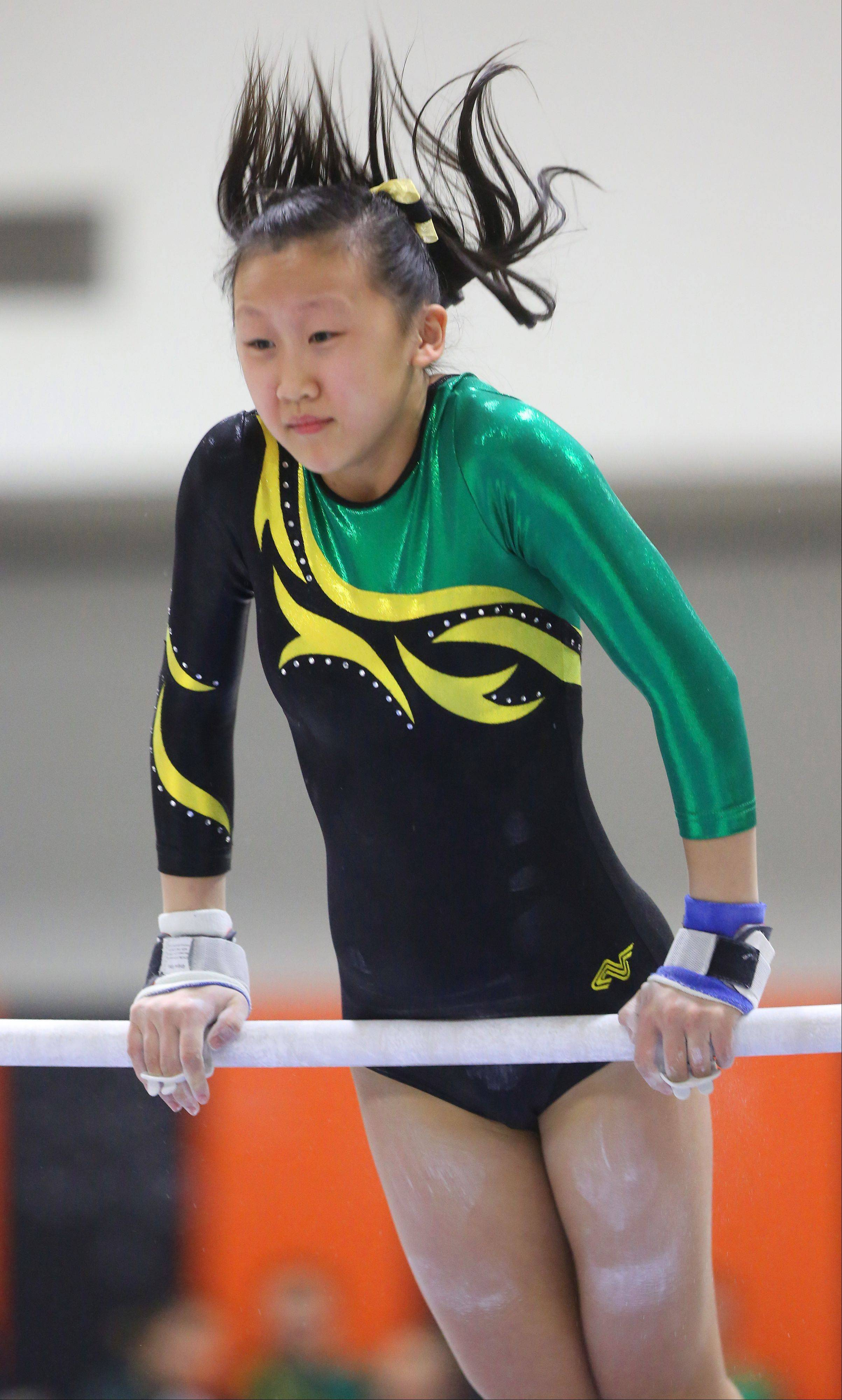 Waubonsie Valley's Allison Yu competes in the uneven parallel bar routine during the Illinois Best Girls Gymnastics Invitational at Wheaton Warrenville South High School.