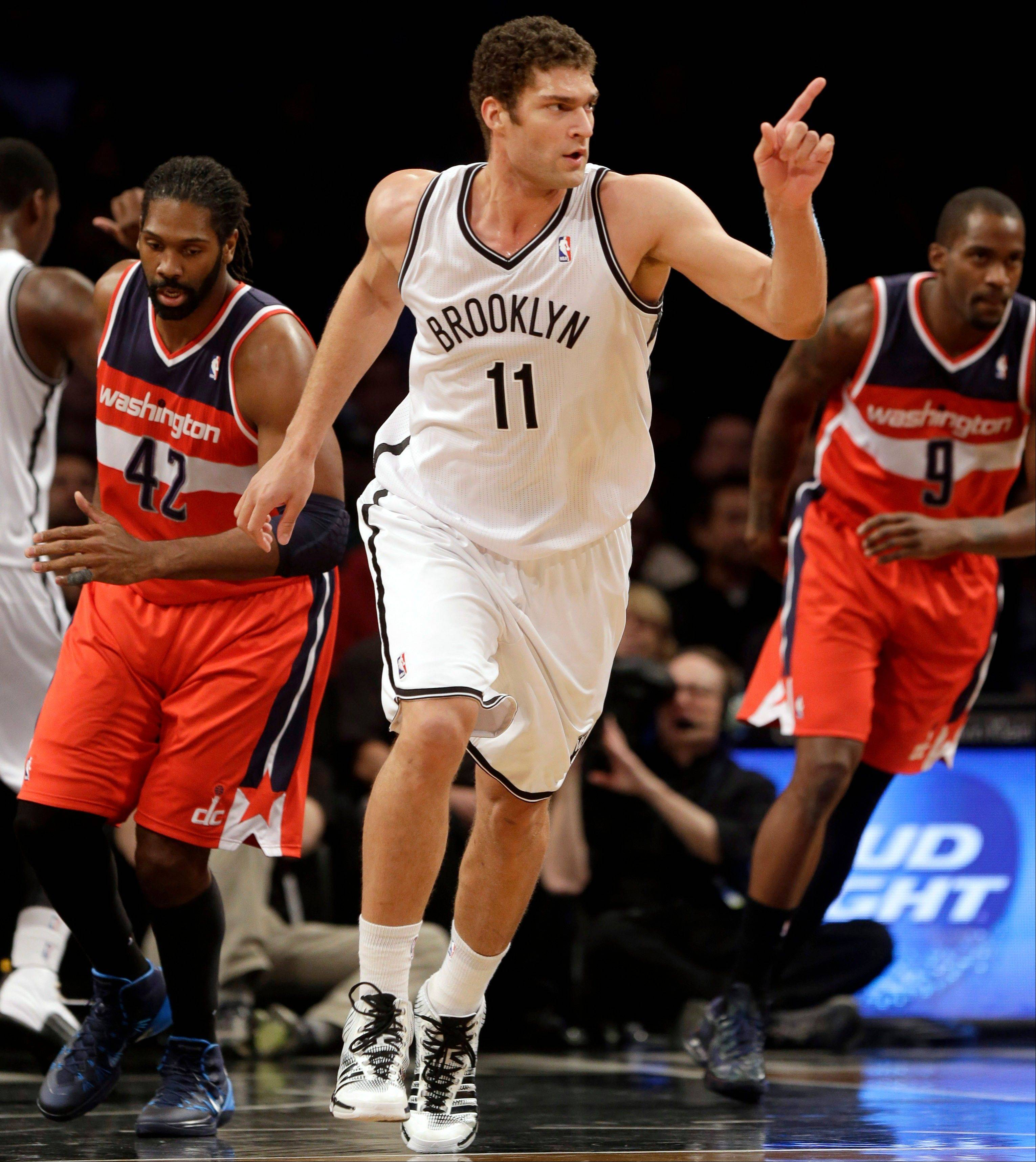 Brooklyn Nets' Brook Lopez points after scoring during the first half of an NBA basketball game against the Washington Wizards on Wednesday, Dec. 18, 2013, in New York.