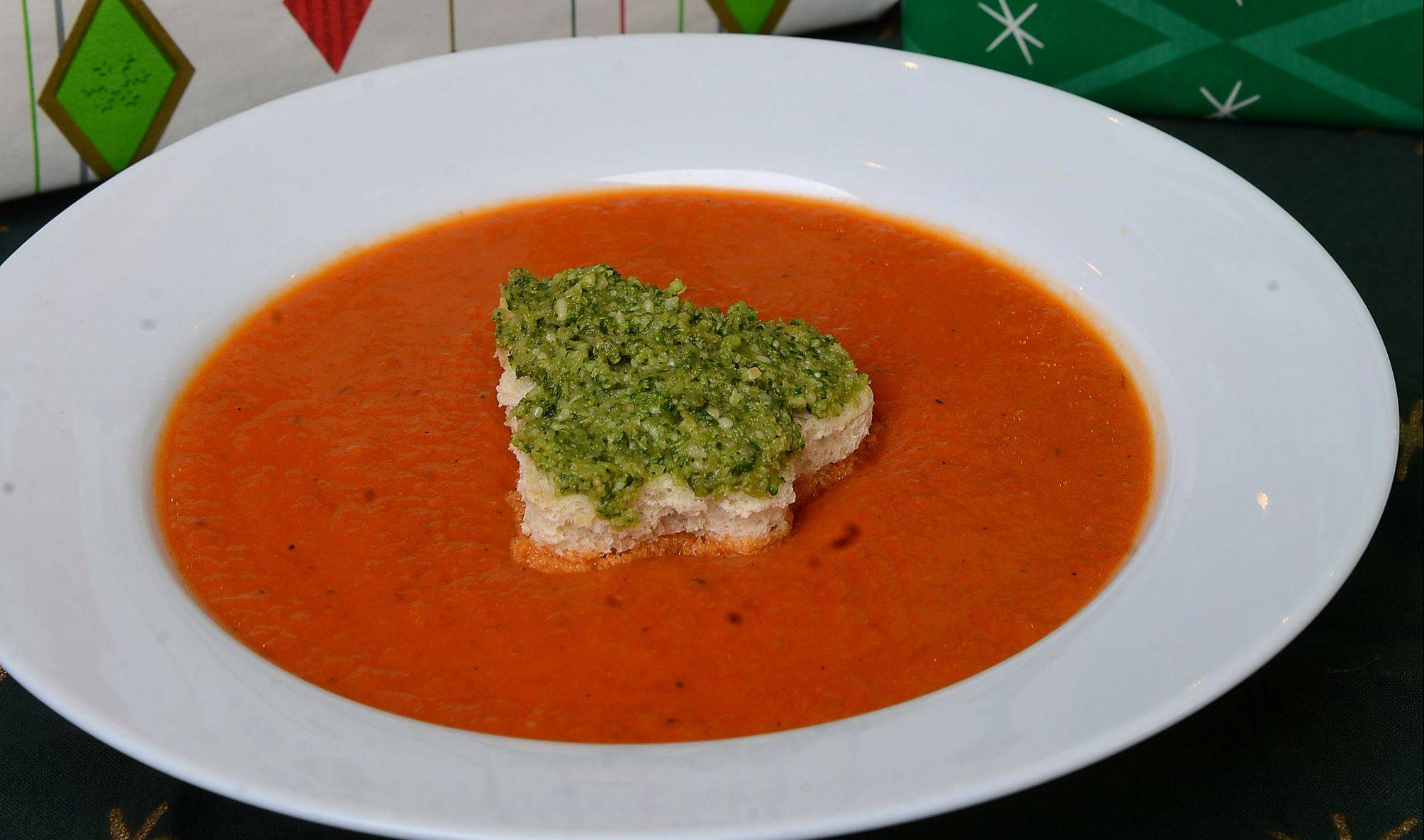 Broccoli pesto spread on Christmas tree croutons make roasted red pepper soup extra festive.