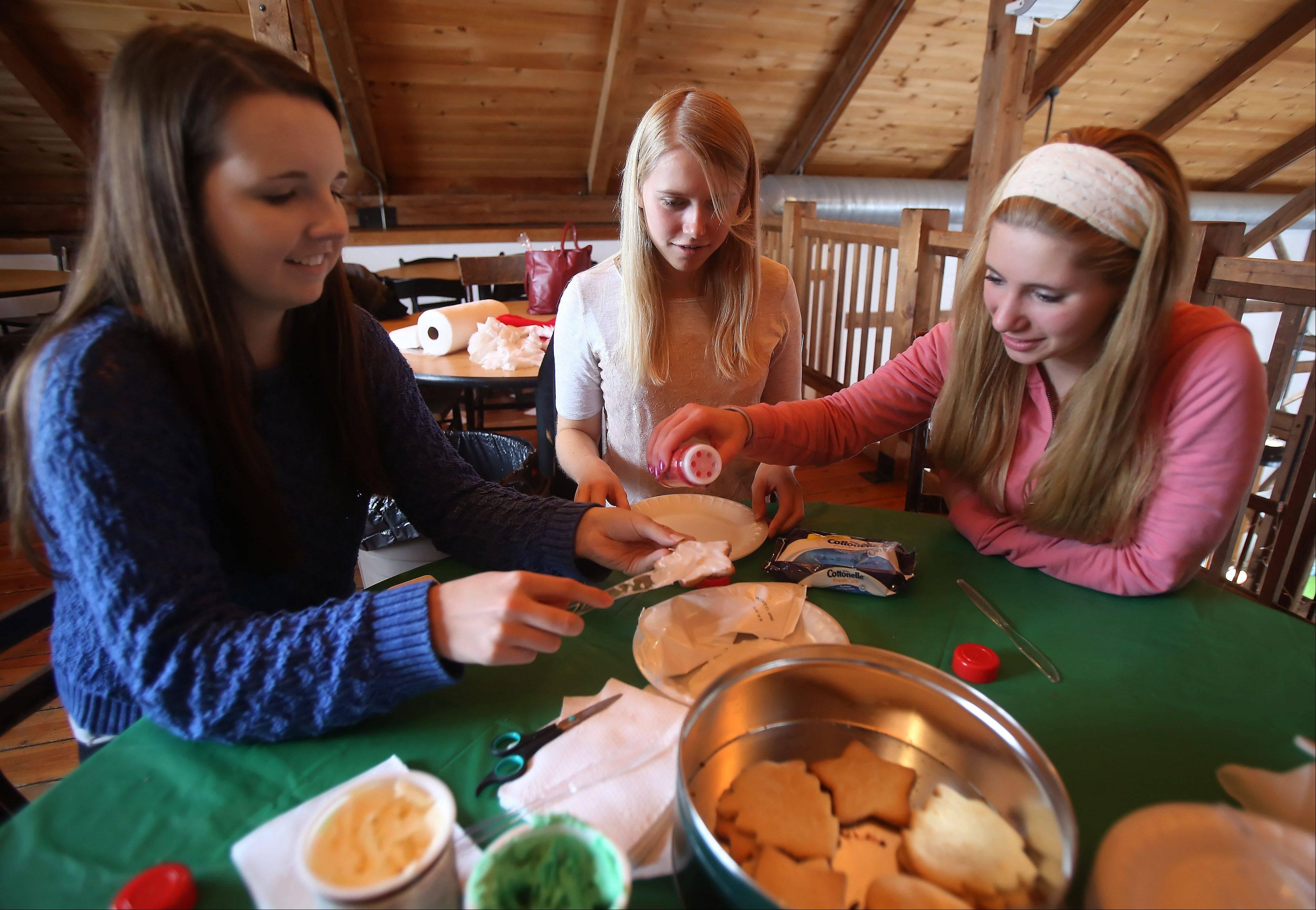 Amanda Jung, left, Hannah Dwinell and Rachel Biersdorf, all of Grayslake, decorate cookies in Santa�s Workshop during the 18th annual Prairie Crossing Cookie Walk and Bake Sale Sunday at Byron Colby Barn in Grayslake. Visitors could choose from thousands of homemade cookies, as well as handmade gifts and unique items from local artisans and merchants.