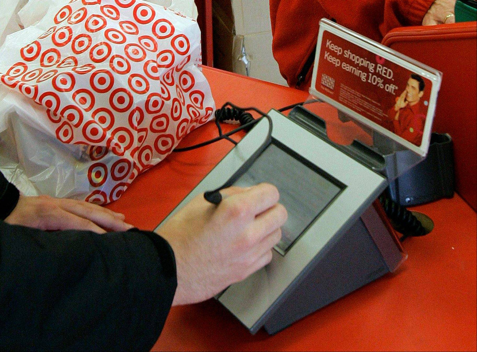 A customer signs his credit card receipt at a Target store in Tallahassee, Fla. Target and other U.S. retailers are ripe for credit card fraud because U.S. card companies use technology easily compromised.
