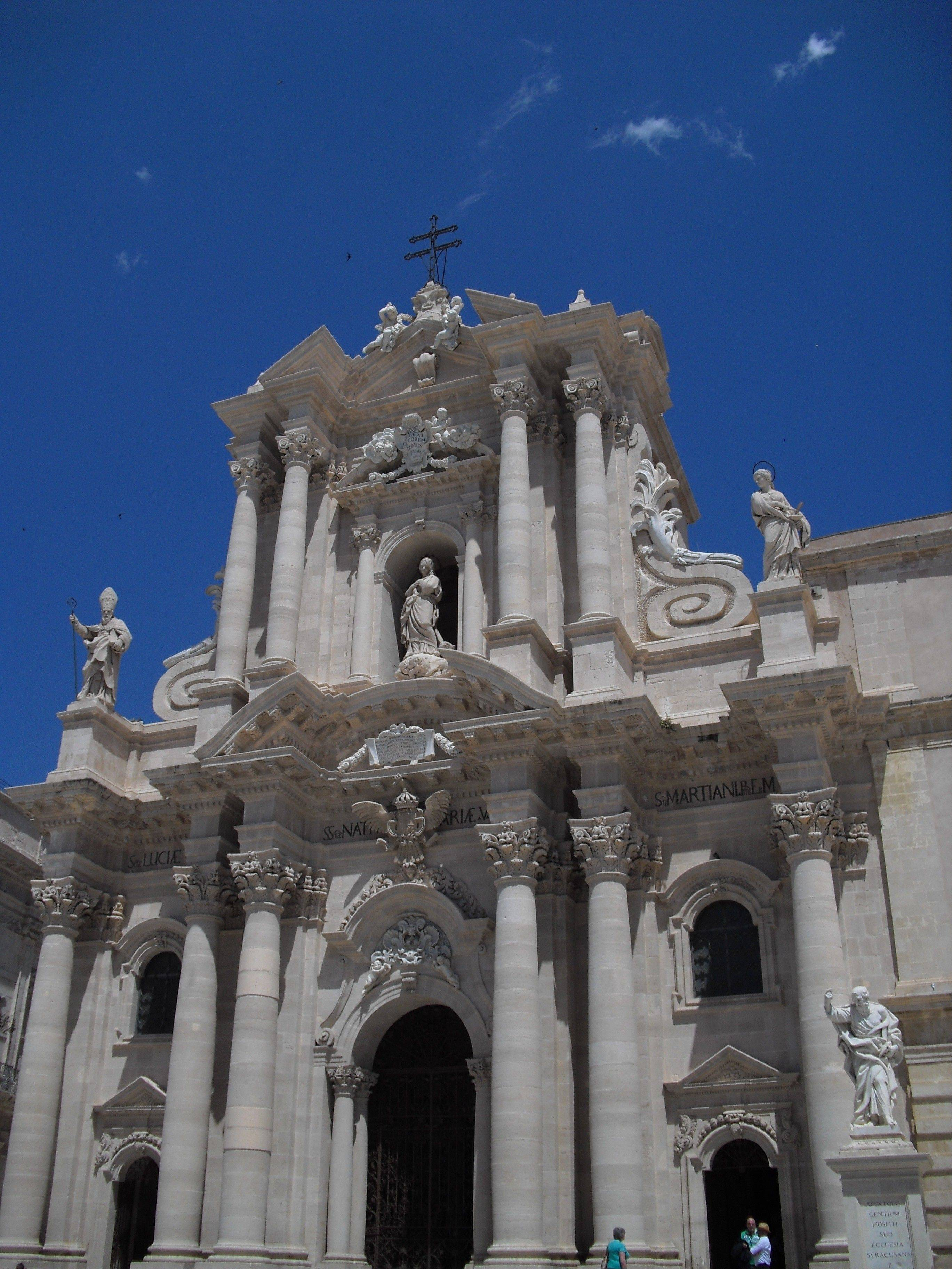 Fans of architecture and history can take in the elaborate baroque facade of the cathedral in the Piazza del Duomo on the Sicilian island of Ortygia. The cathedral's origins as a Greek temple to the goddess Athena are clear by the Doric columns that peek through the exterior and interior of the building.