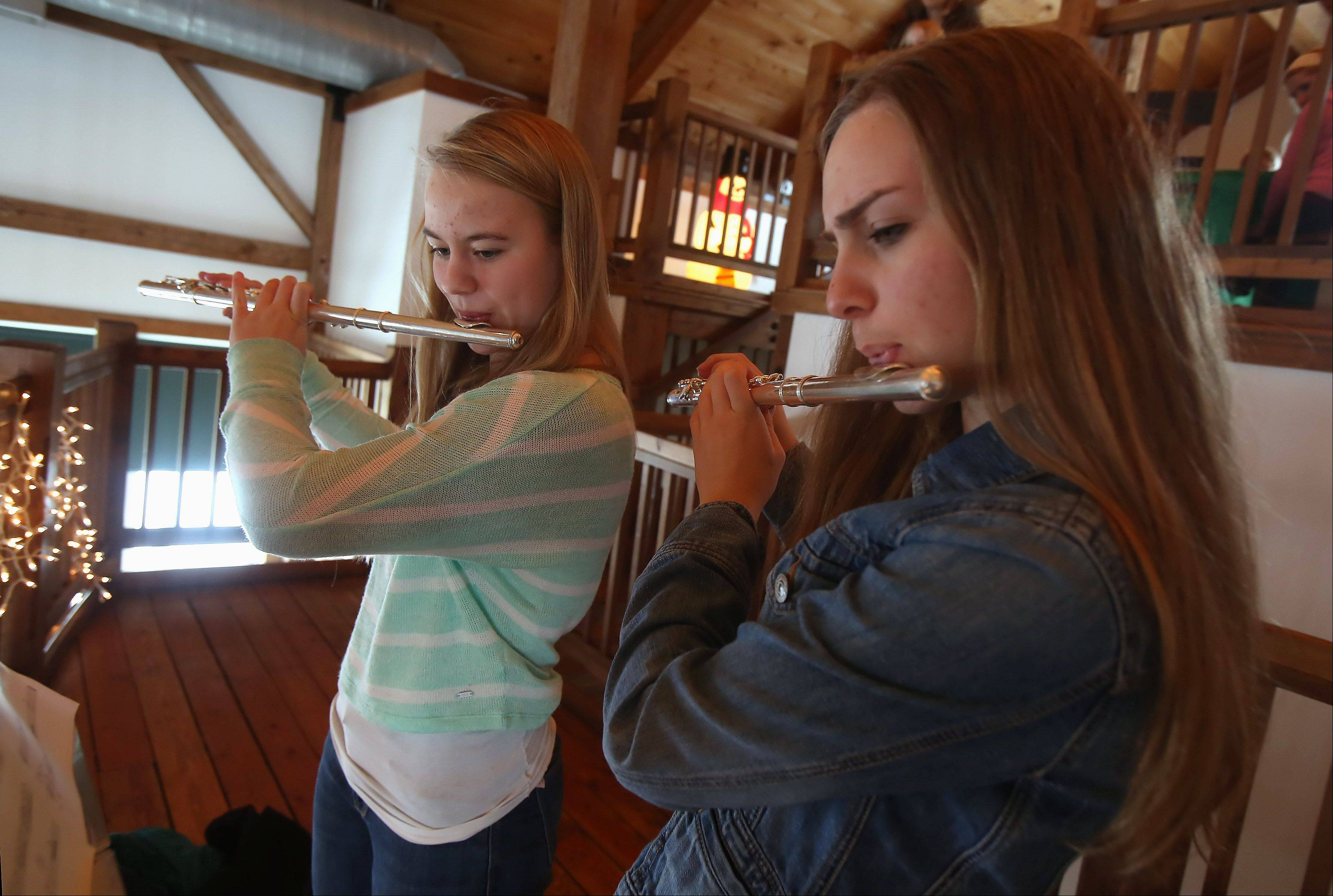 Sarah Johns, left, and Alyssa Remshak, both 16, play flutes as they entertain visitors with holiday music during the 18th annual Prairie Crossing Cookie Walk and Bake Sale Sunday at Byron Colby Barn in Grayslake. Visitors could choose from thousands of homemade cookies as well as handmade gifts and unique items from local artisans and merchants.
