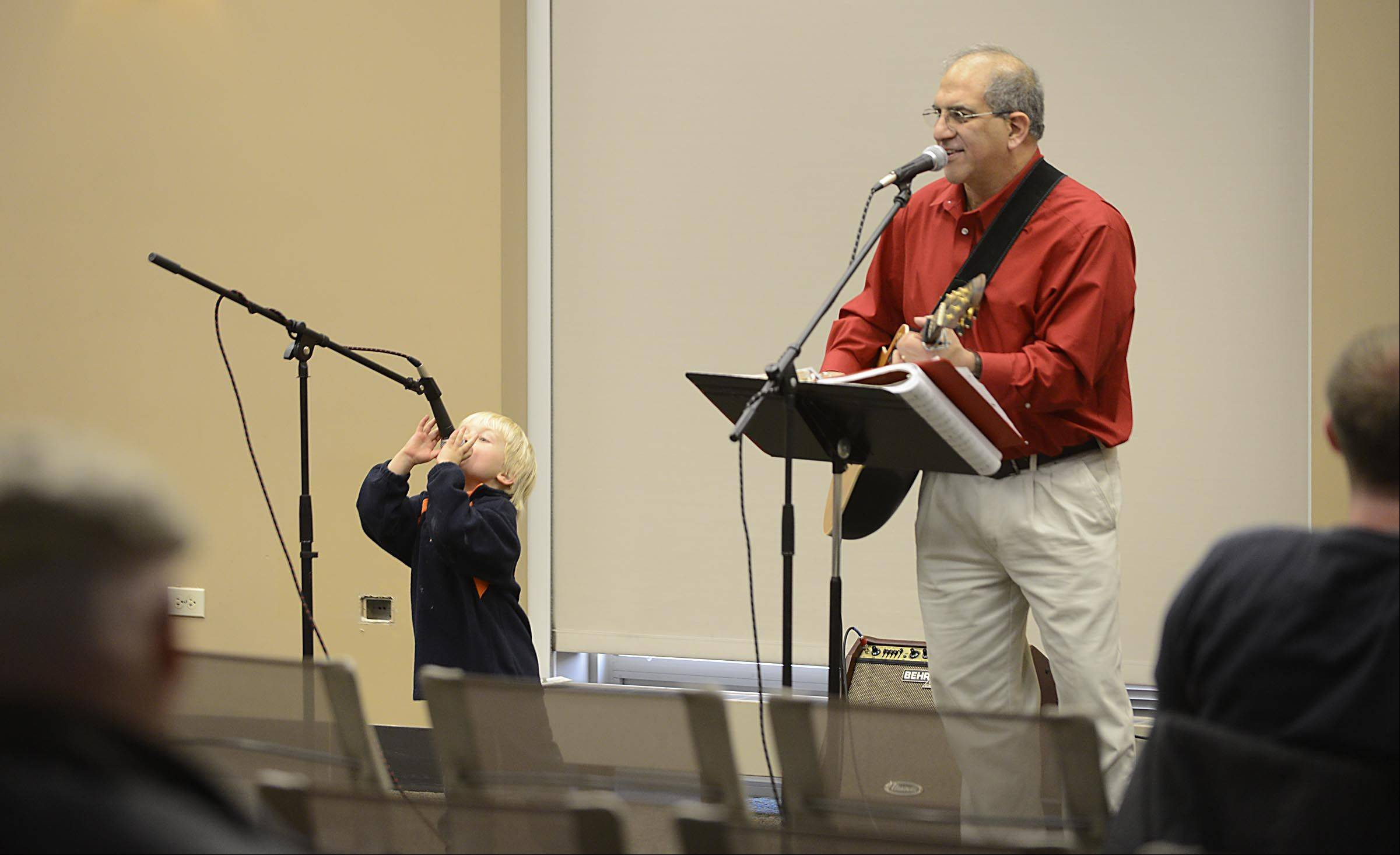 "Musician Tom Malouf sings Christmas carols Sunday as Miles Carlson, 3, joins him from his front row seat at the Batavia Public Library. Miles' mother Jodi, of Batavia, said, ""He's got the spirit!"""