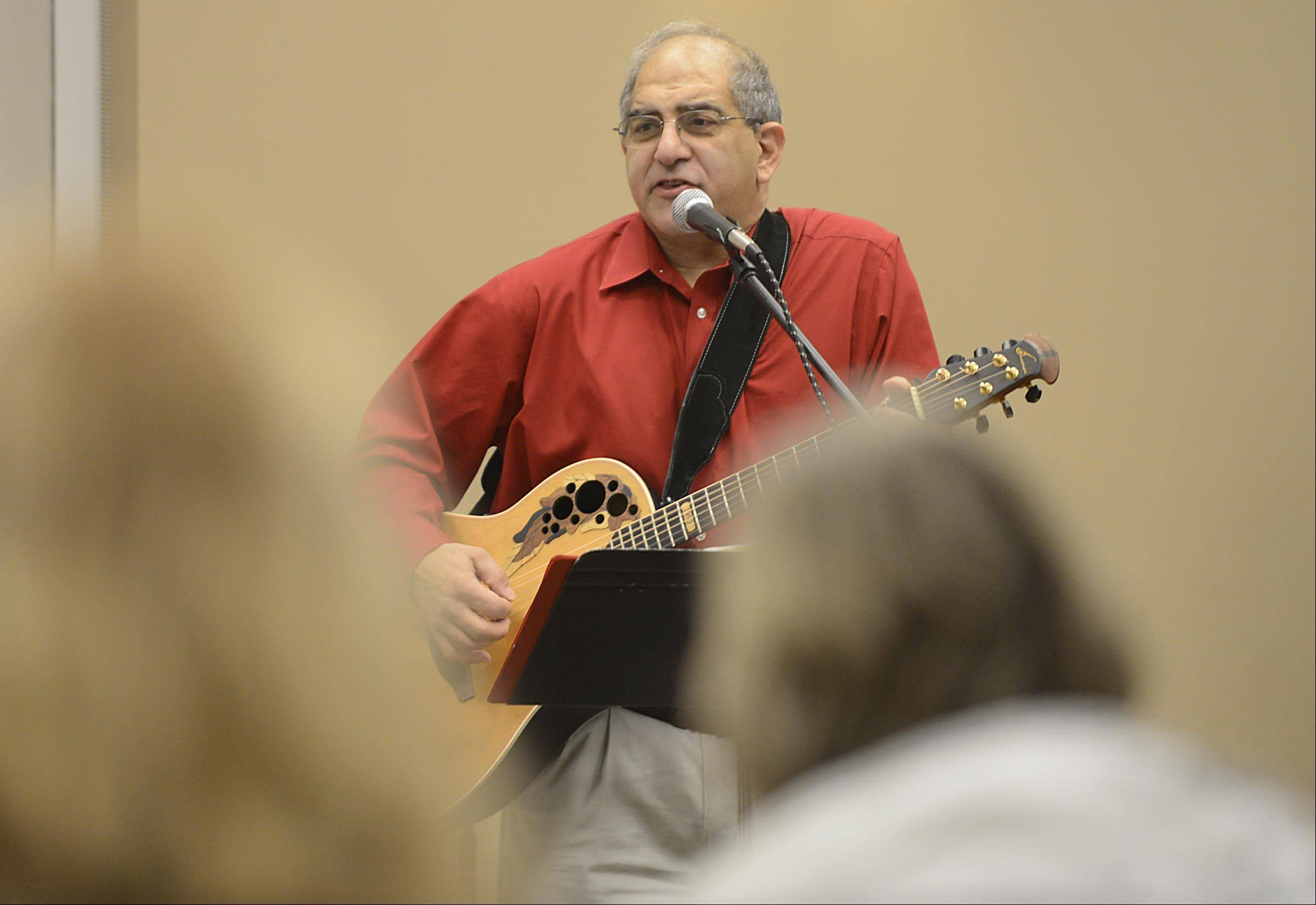 Musician Tom Malouf, of Roselle, sings Christmas carols Sunday at the Batavia Public Library. He had guest appearances onstage, including his daughter, puppets, and Santa Claus.