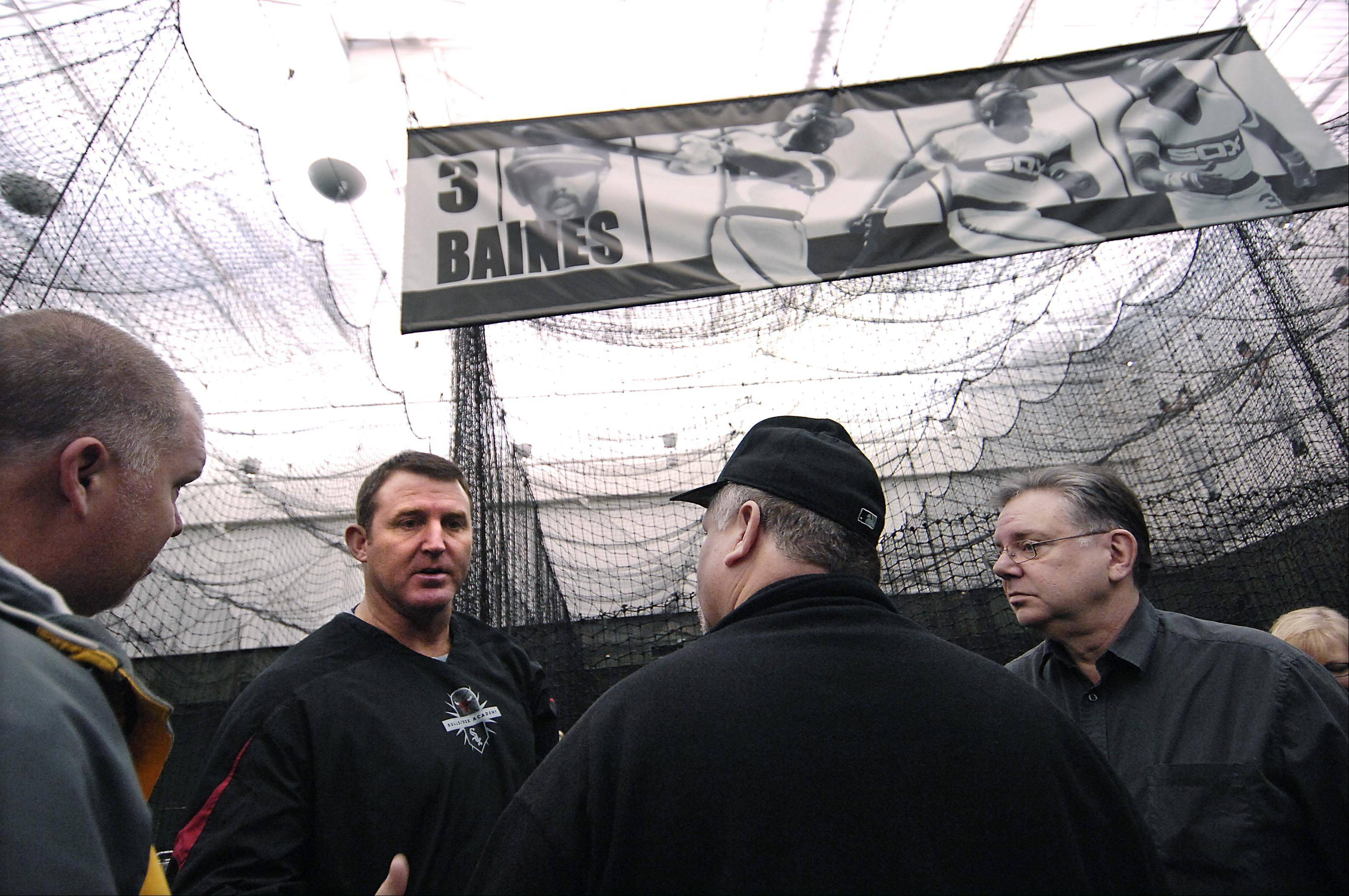 Five-time Major League Baseball All-Star and former Chicago White Sox slugger Jim Thome talks with the fathers of young players Sunday at the Chicago Bulls/White Sox Academy in Lisle. Thome, who still works for the White Sox organization, was putting on hitting clinic for young players.