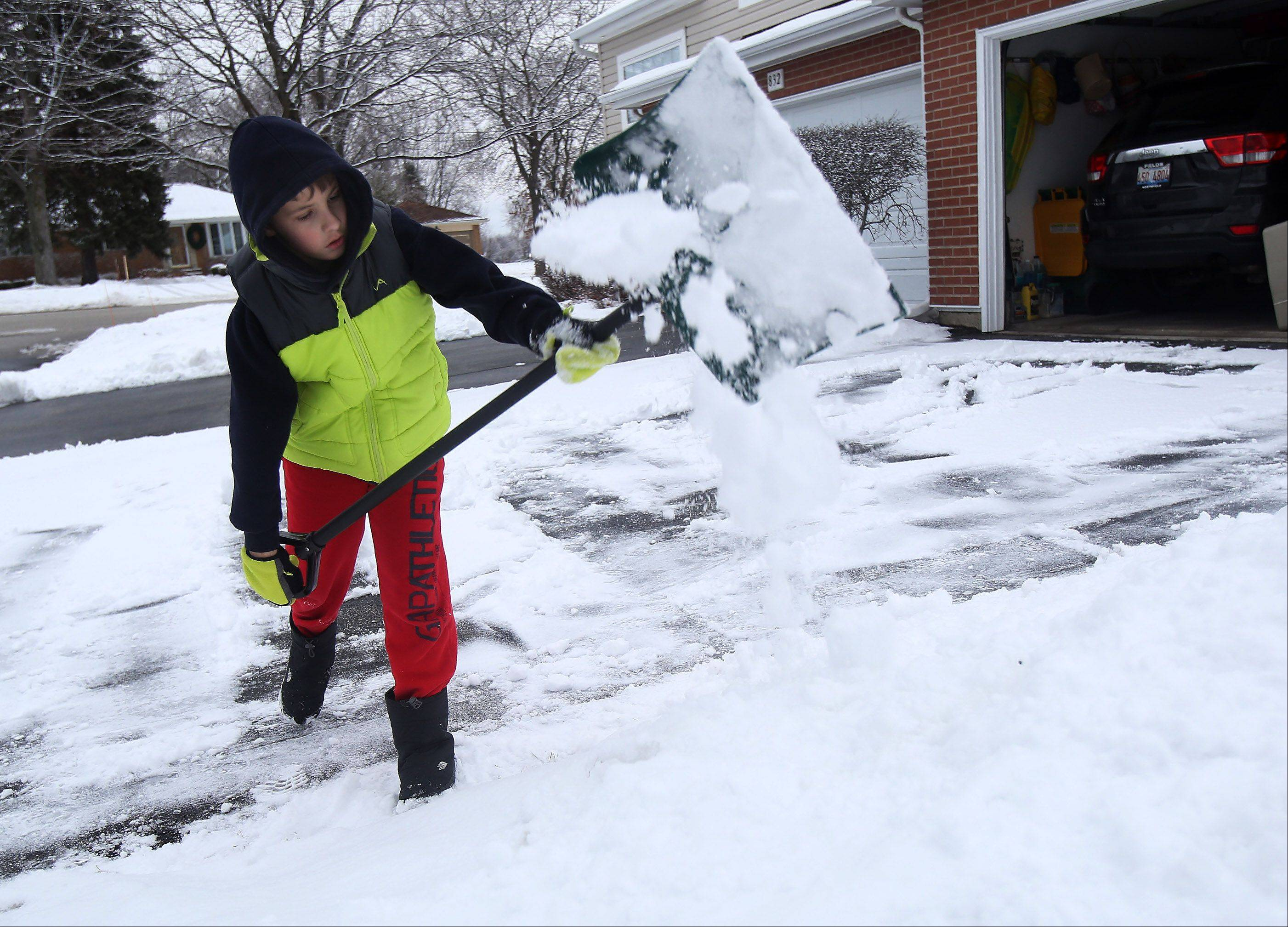 Buffalo Grove resident Mario Musa, 10, shovels the snow off his driveway Sunday after overnight snow and sleet covered the area. Towns in the North and Northwest suburbs were heaviest hit by snow Sunday.