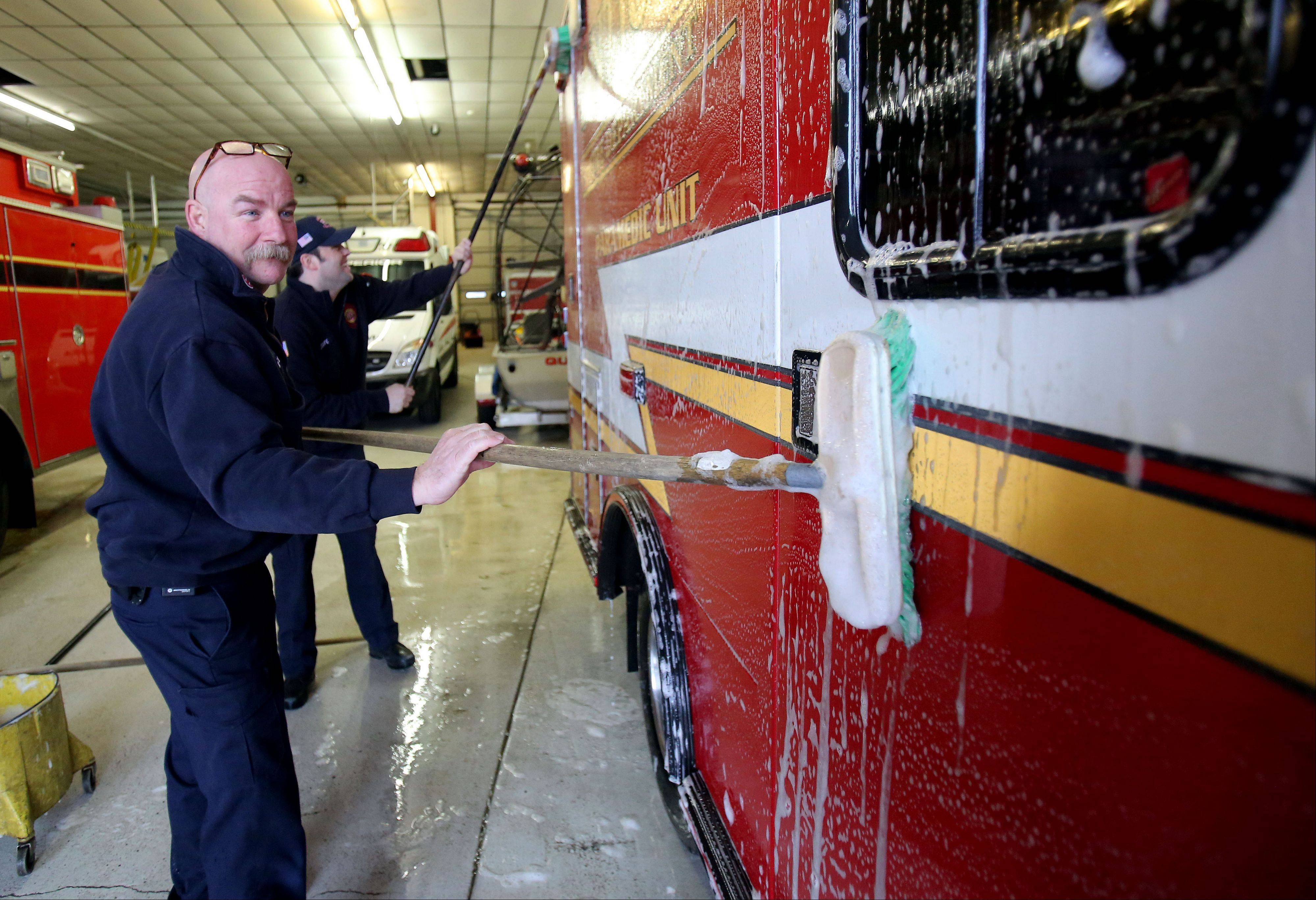 Antioch Fire Capt. Dave Nellessen, left, and firefighter Justin Scaife wash an ambulance at the Antioch Fire Station. Most area fire stations, equipment and fire trucks are co-owned by the First Fire Protection District and the Antioch Volunteer Fire Department.