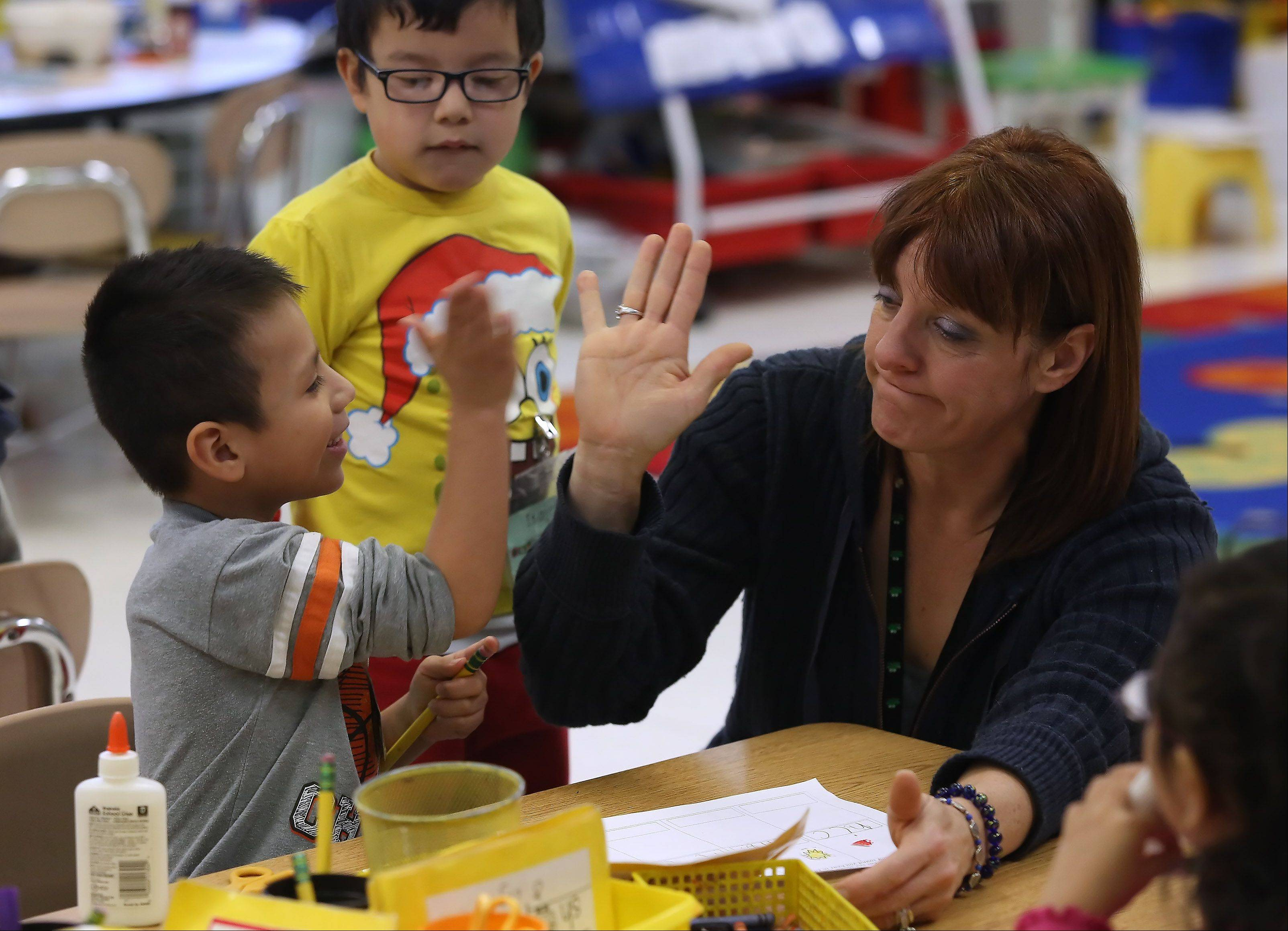 "Kindergarten teacher Annette McCafferty works with Romulo Barrios in her dual-language class at Woodland Primary School in Gages Lake. Woodland Elementary District 50 is among several suburban districts adjusting to a ""minority majority"" population."