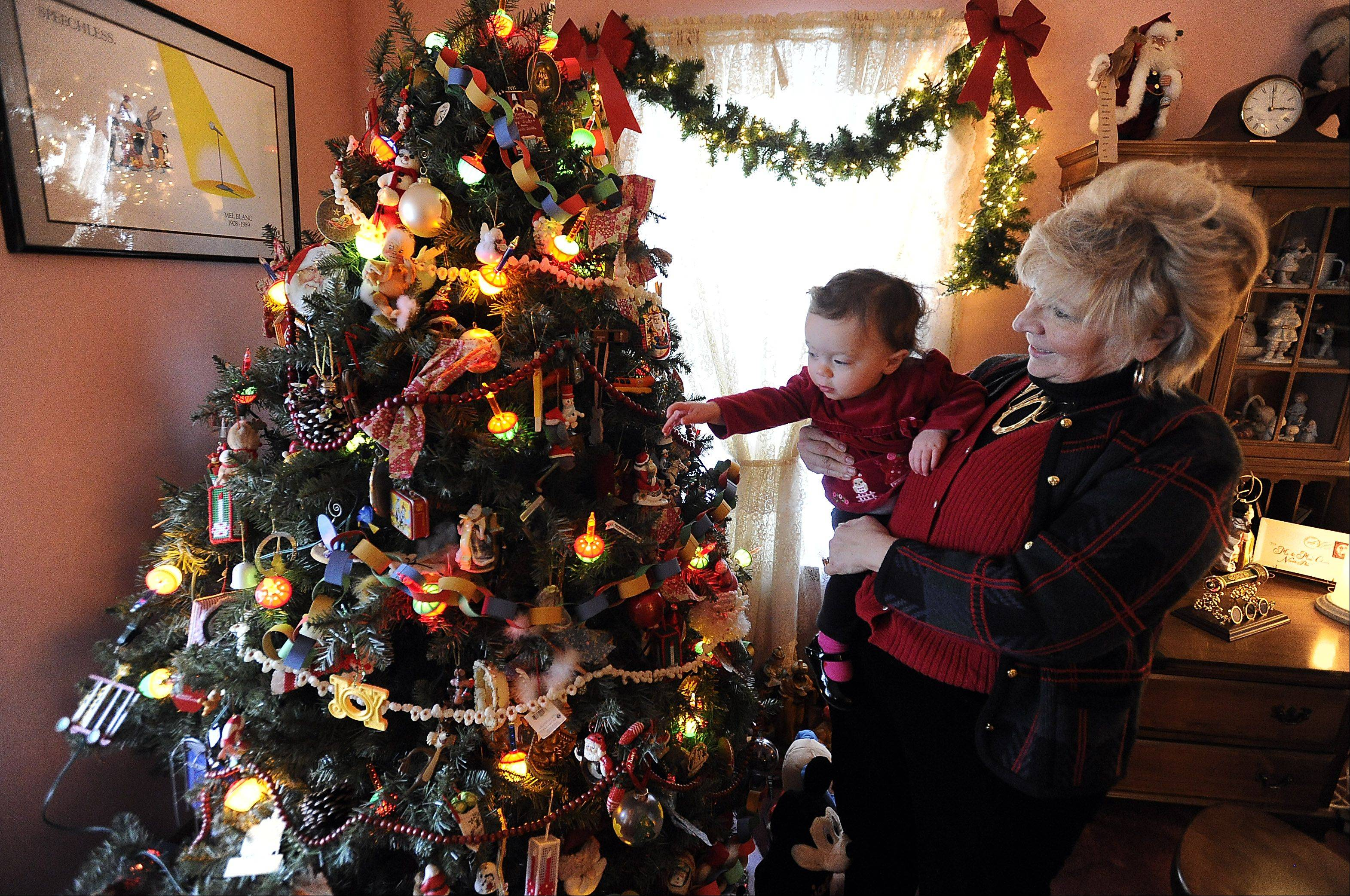 Mary Ann Sesko holds her 18-month-old granddaughter, Gabrielle Dyckman, whose favorite Christmas tree wears bubbling lights.
