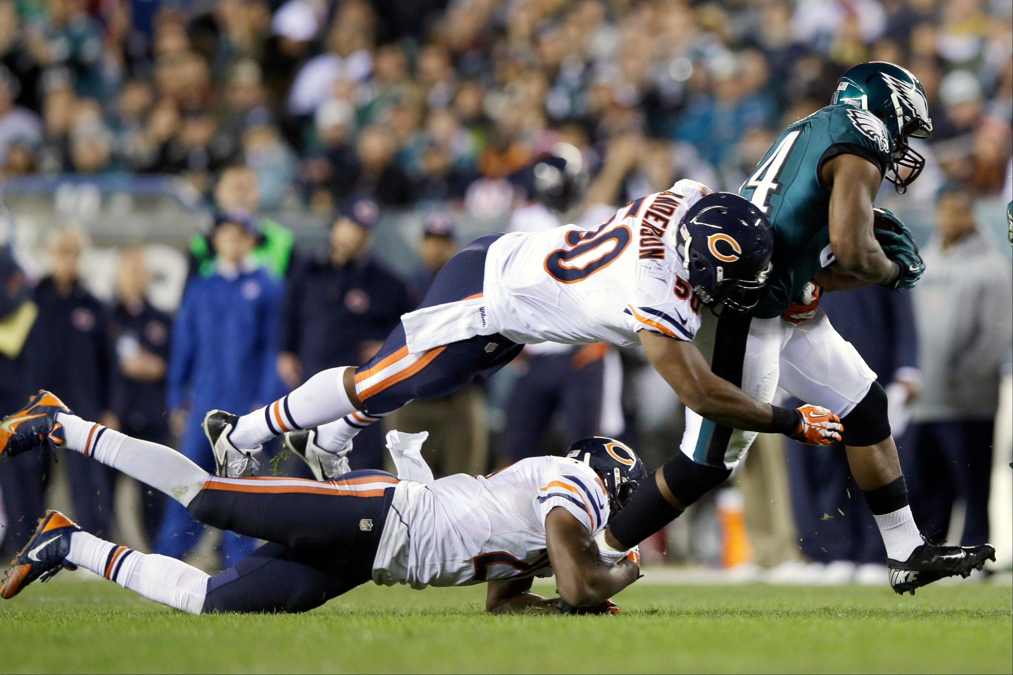 The Philadelphia Eagles' Bryce Brown, right, breaks free of Bears James Anderson, top left, and Roc Carmichael during the second half of an NFL football game, Sunday, Dec. 22, 2013, in Philadelphia.
