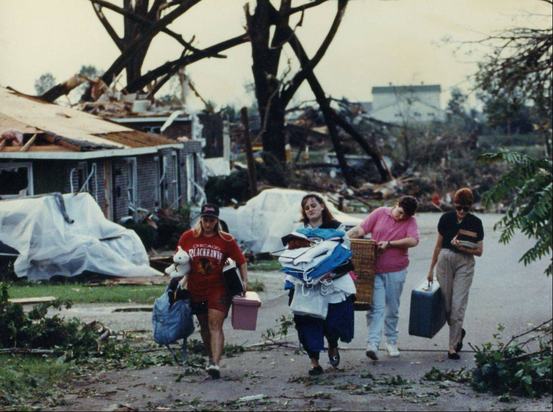 Plainfield residents carry their possessions after a tornado destroyed their home in 1990.