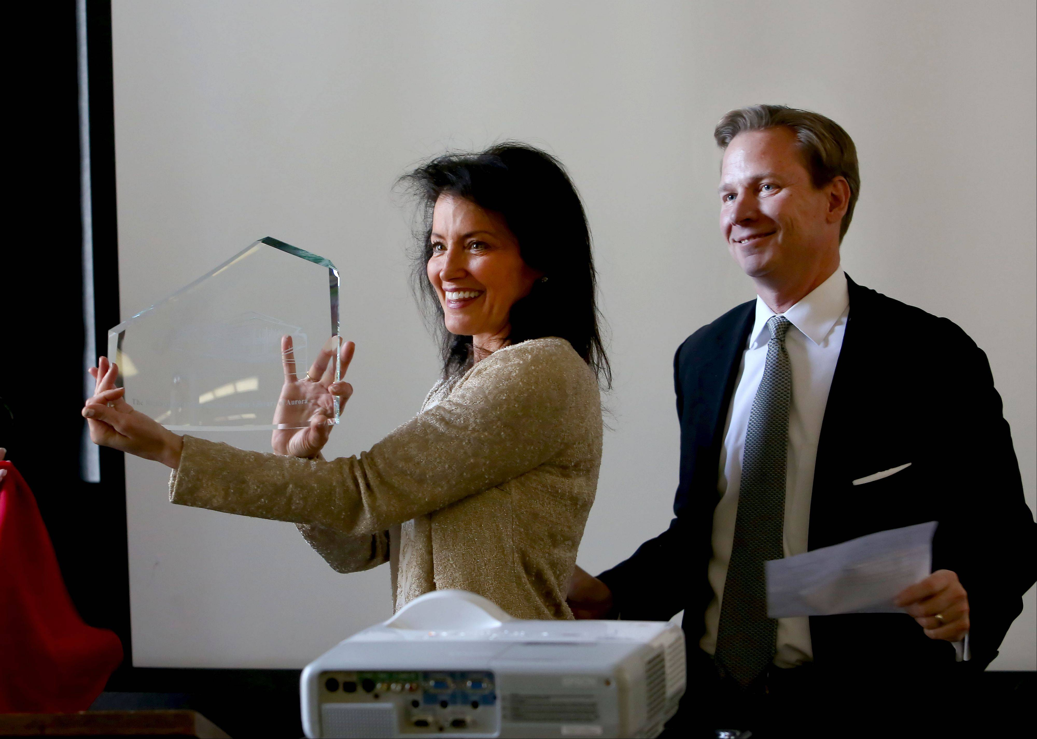 Gina Santori, with Aurora Public Library President John Savage, holds a glass replica of the proposed downtown library, given to her Monday after it was announced the Richard and Gina Santori Charitable Foundation donated $3 million to the Aurora Public Library Foundation to establish a technology endowment.