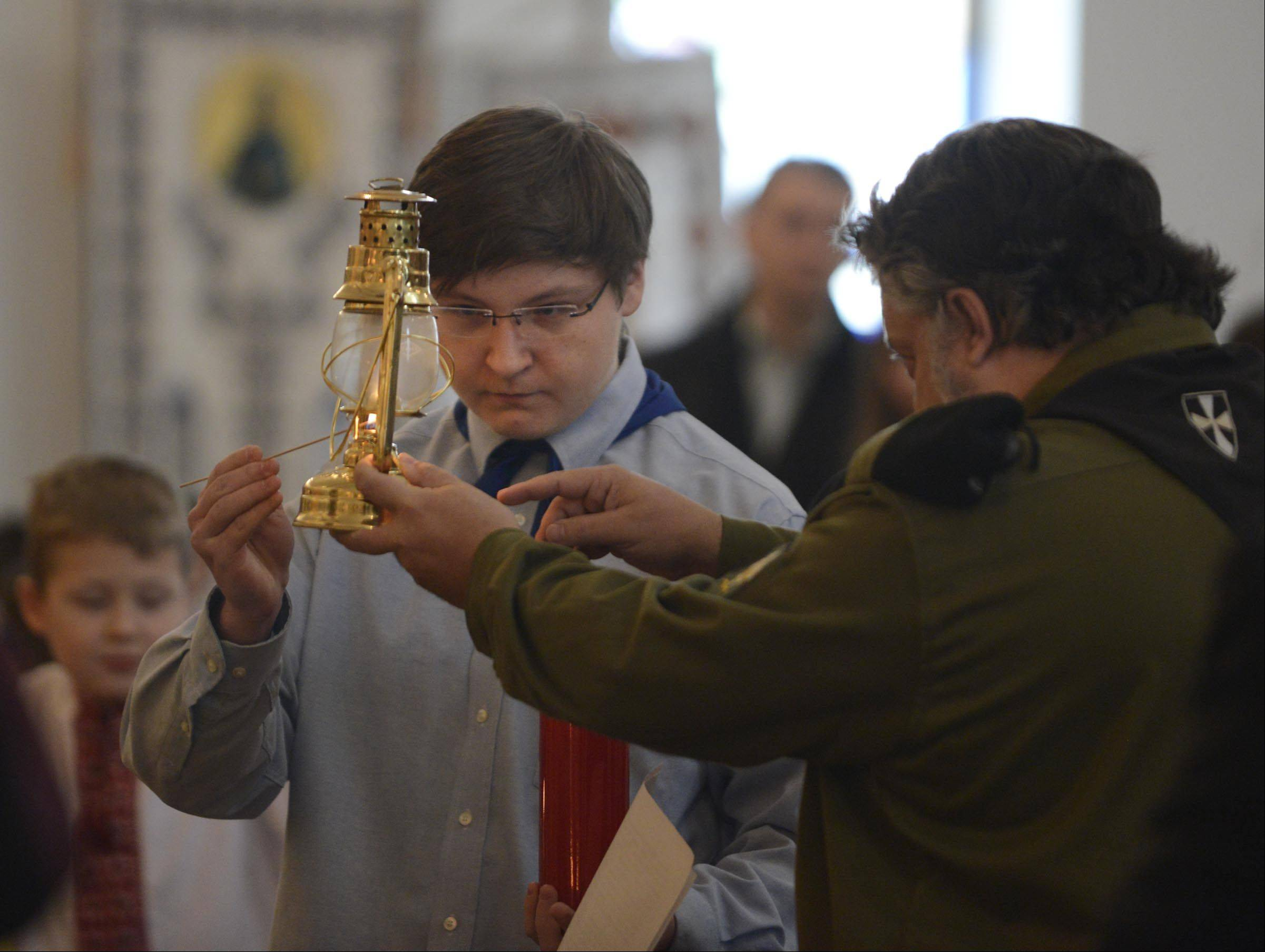 Ukrainian Scout leader Yuriy Zajac shares a flame Sunday from the birthplace of Jesus in Bethlehem with Simon Mischenko of the Ukrainian Democratic Youth Organization at St. Andrew Ukrainian Orthodox Cathedral in Bloomingdale. The Bethlehem Peace Light has been burning at the same spot in Bethlehem for more than 1,000 years and is split and travels around the world, available to anyone who wants to take the flame during the holy time around Christmas.