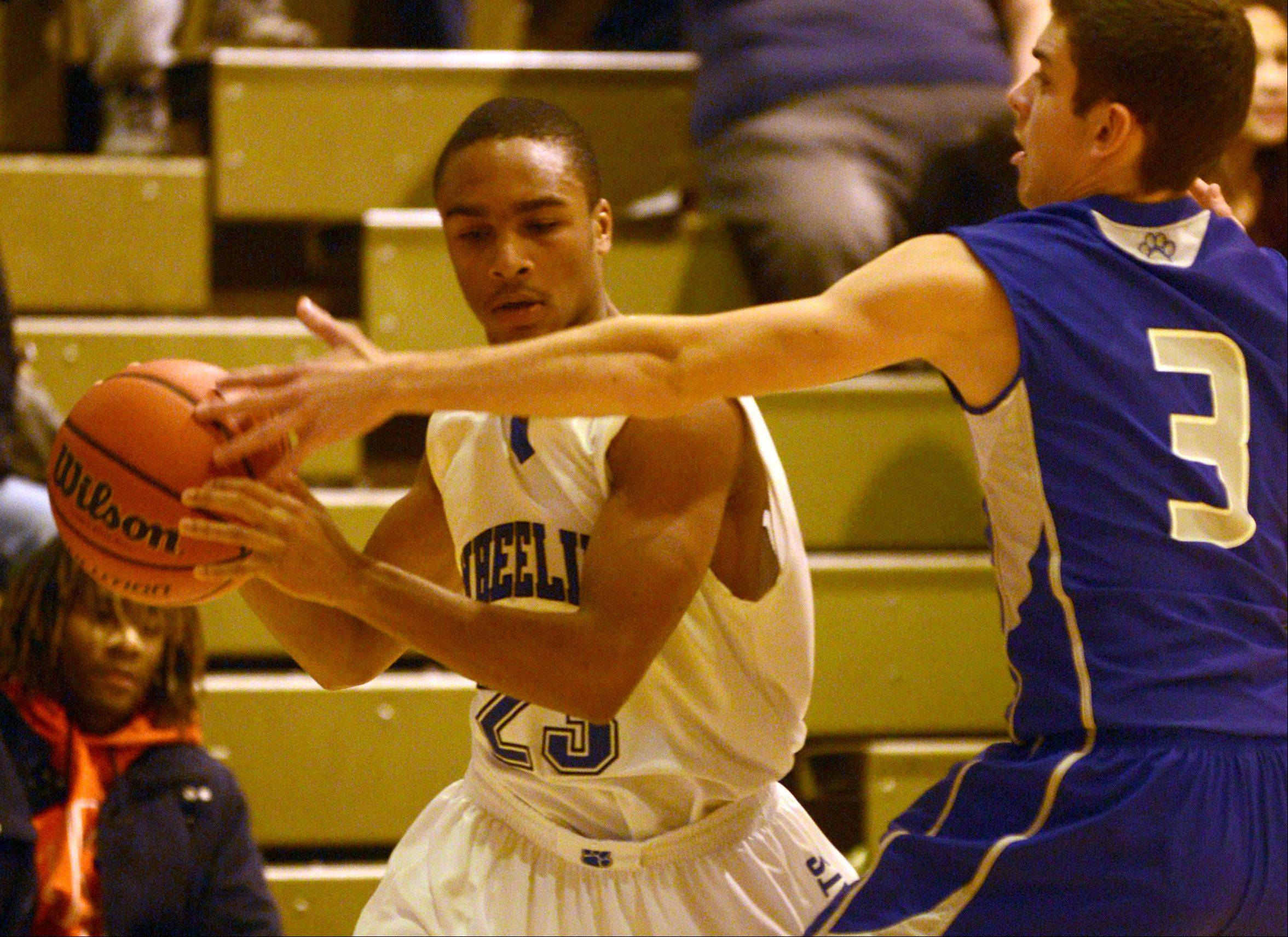Vernon Hills� Michael Mariella, right, plays defense against Wheeling�s Nate Laude, left.