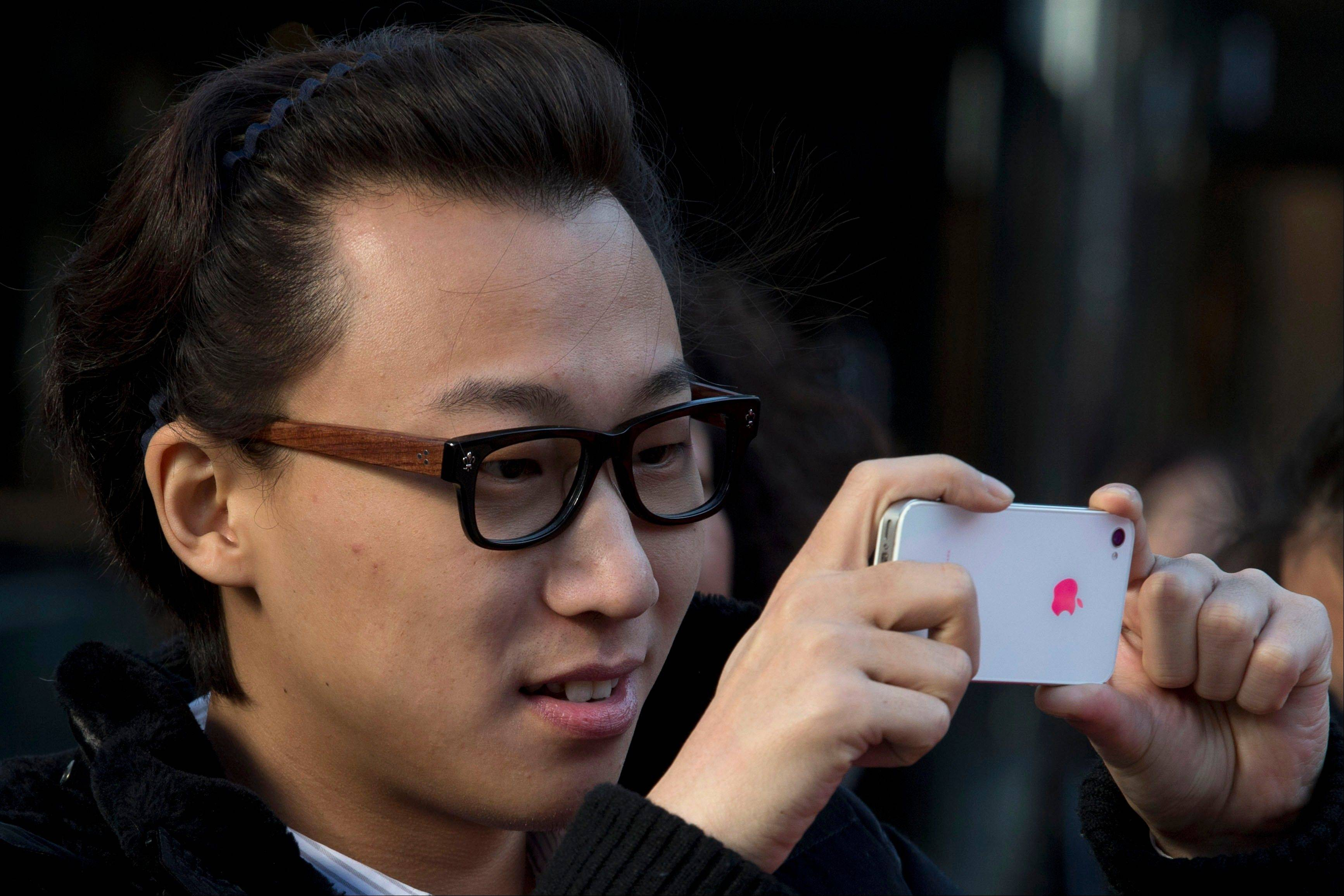 A man uses his Apple iPhone on a street in Beijing Monday. Apple and China Mobile announced a long-anticipated agreement Monday to bring the iPhone to the world's biggest phone company. The iPhone, once hugely popular in China, has been eclipsed by the rise of lower-priced rival smartphones from Samsung and Chinese companies.