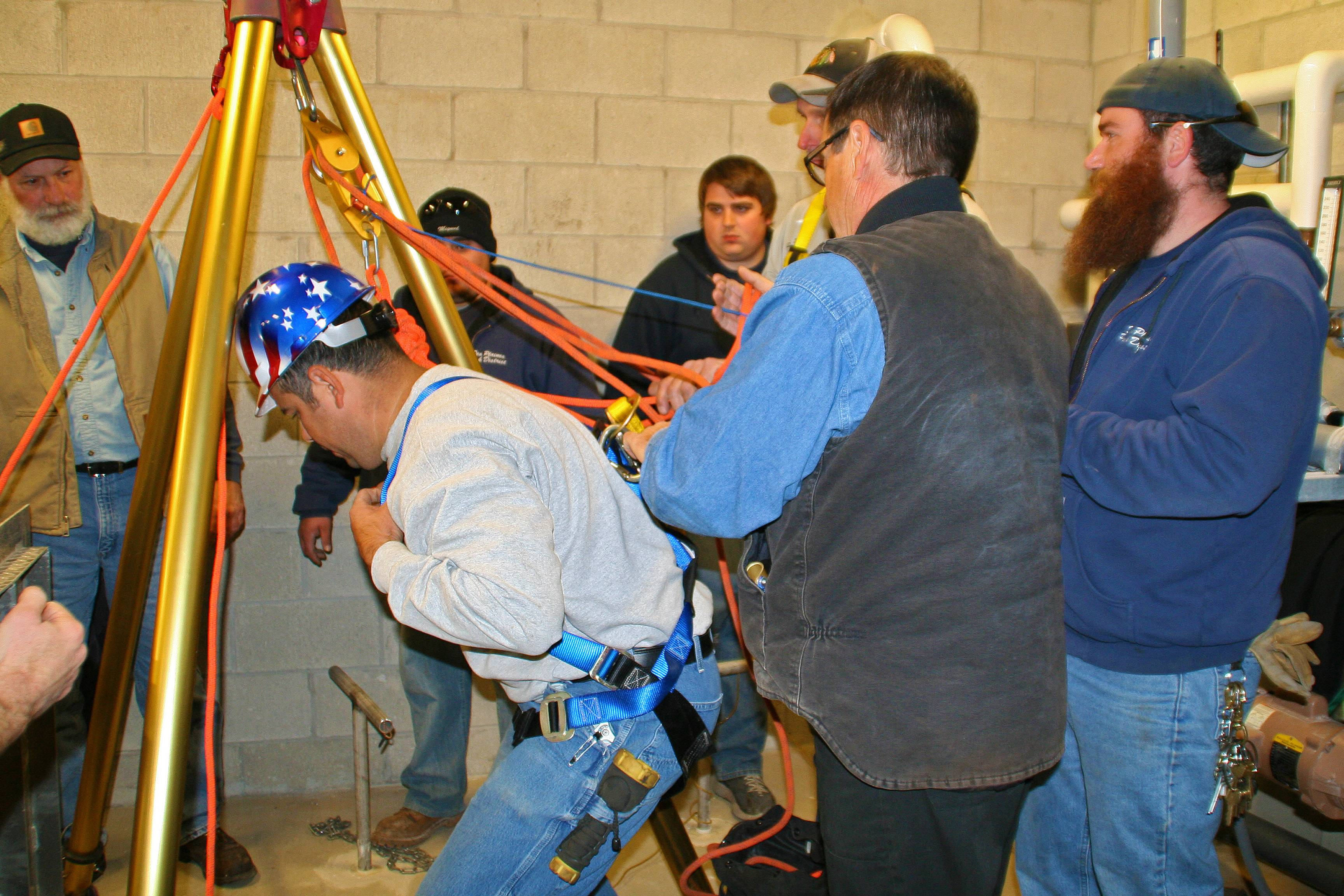 Sesar Botello is clipped into the harness attached to the Des Plaines Park District's entry and evacuation tripod during the Confined Space Entry and Non-Entry Rescue Training conducted by START Group.