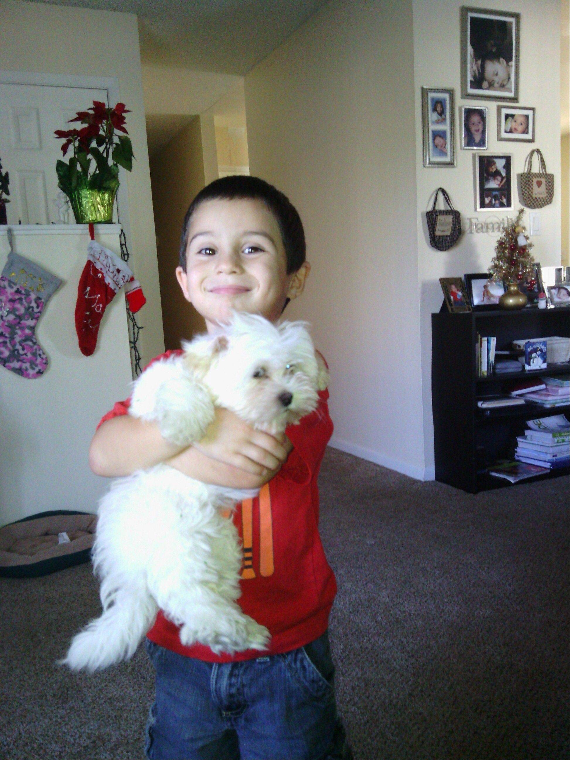 In this family photo released by Melody Russell and provided by the Tampa Police, 5-year-old Marcus Russell holds Honey, the family's 12-week-old Shih Tzu. Police say burglars broke into Melody Russell's home, stole her two children's gifts from under the tree and snatched the family's puppy.